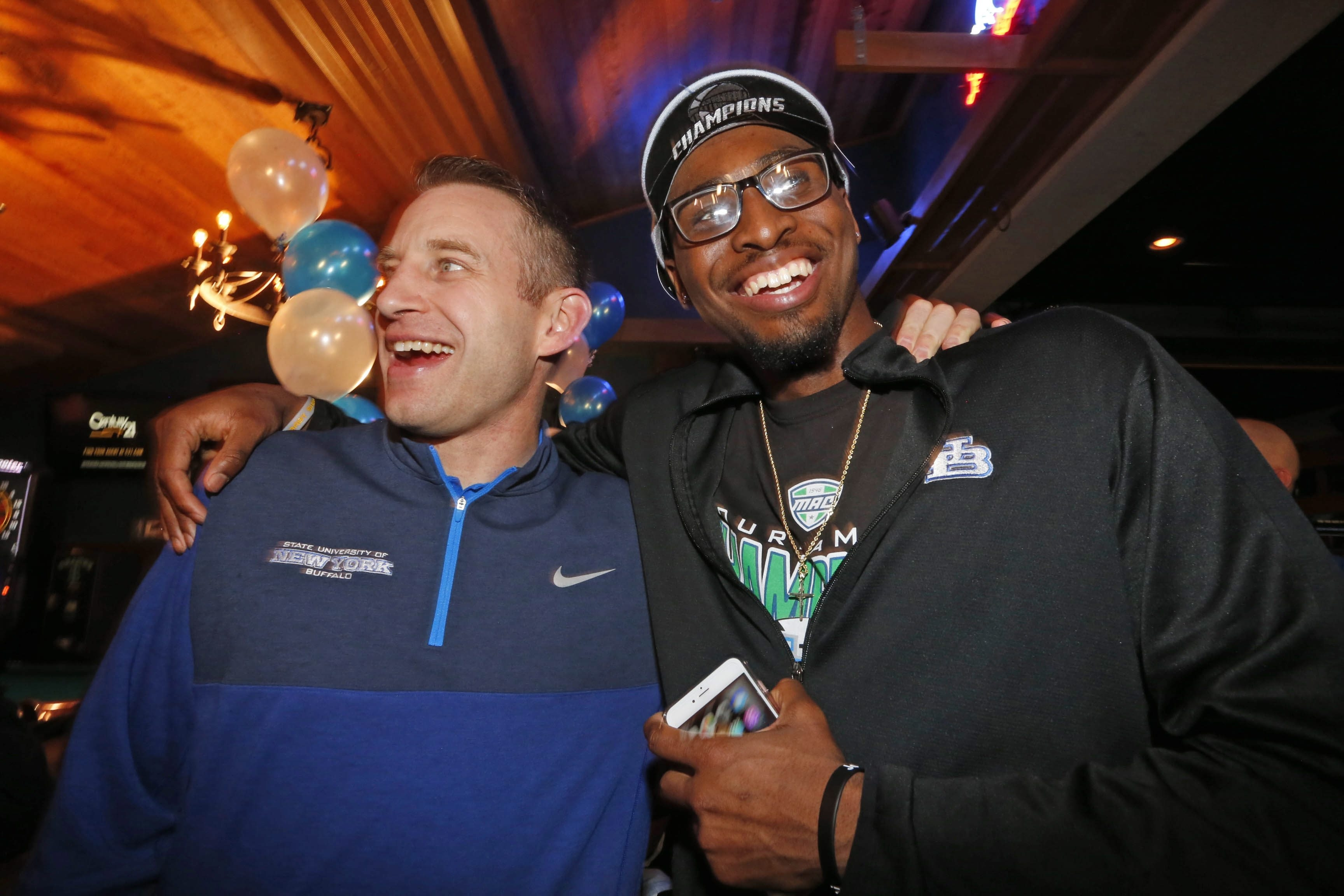 UB men's basketball coach Nate Oats and player Blake Hamilton celebrate the announcement that the Bulls will play Miami in their opening NCAA game.