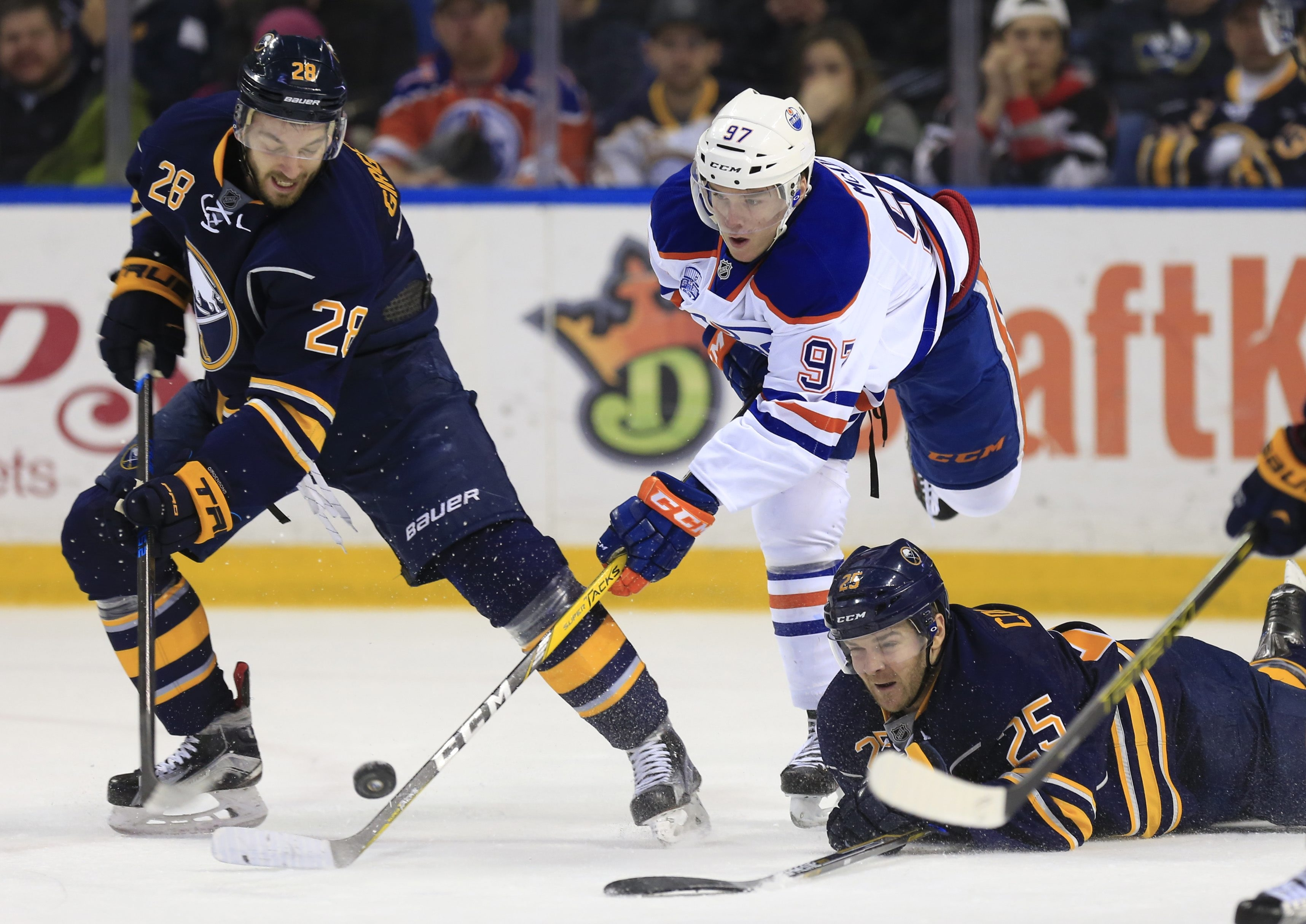 Edmonton's Connor McDavid tries to go after a loose puck between Zemgus Girgensons and a fallen Carlo Colaiacovo in the first period Tuesday at First Niagara Center.