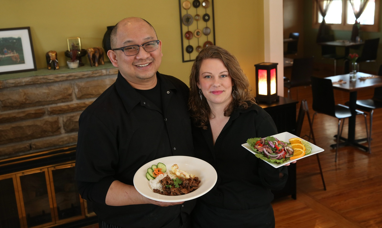 Water Lily Cafe owners Kim and Amy Suphankomut present the Thai garlic-pepper pork with fried egg and the spicy beef salad.  (Sharon Cantillon/Buffalo News)