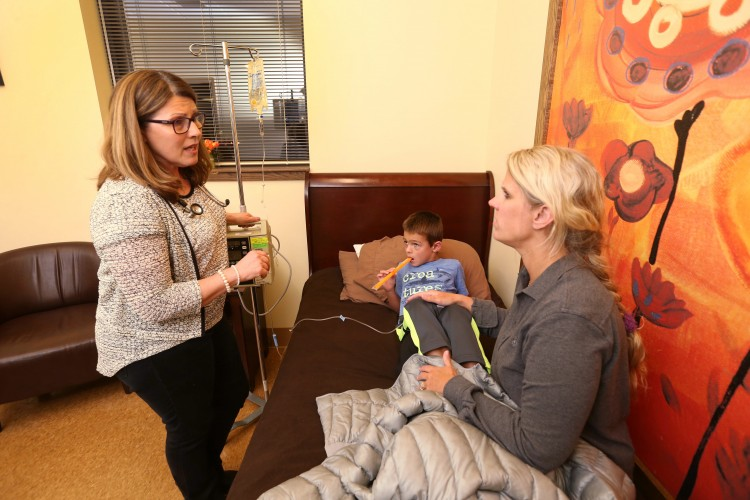 Nurse practitioner Becky Roloff takes care of Andrew Jakubowski, 6, of Lancaster at Pediatric  and Adolescent Urgent Care of WNY which is open on nights and weekends to give families an alternative to the emergency room.  His mom Kristen Jakubowski sits on the bed with him as he gets an IV.   (Sharon Cantillon/Buffalo News)