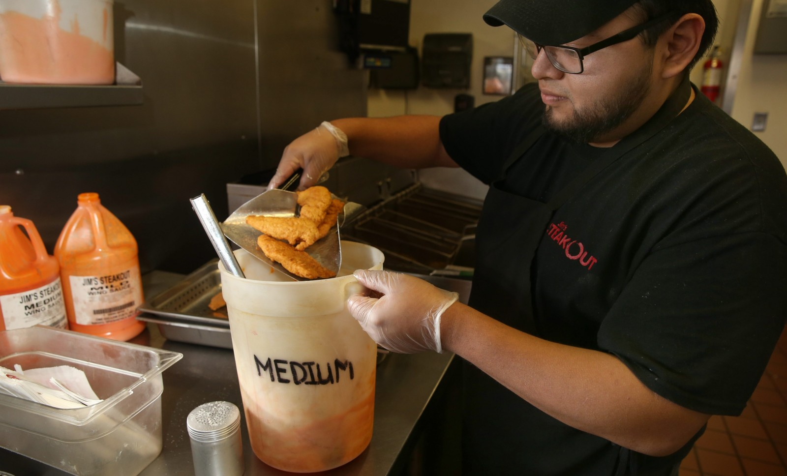 Jim's Steakout cook Alfredo Castaneda dips the deep-fried chicken fingers go into the hot sauce. (Sharon Cantillon/Buffalo News)