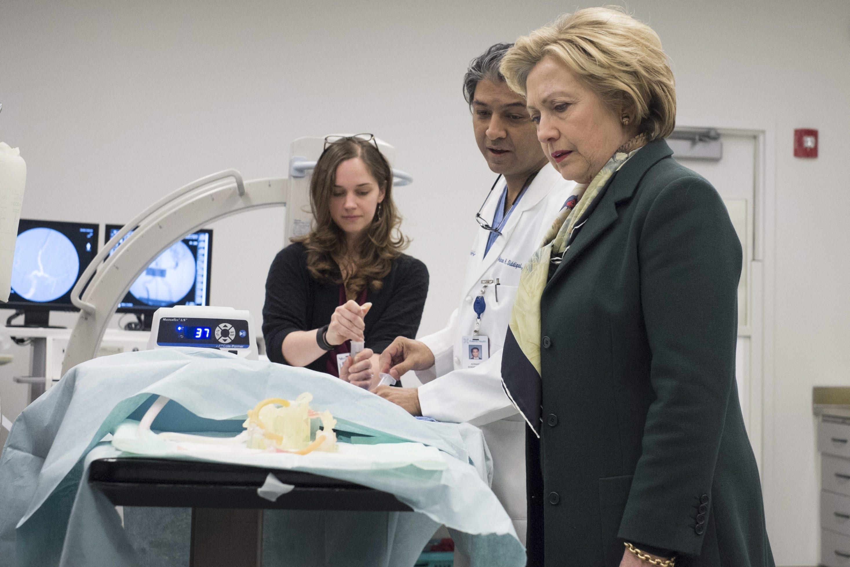 Dr. Adnan Siddiqui, chief medical officer of the Jacobs Institute, gives a demonstration of technology to presidential candidate Hillary Clinton during a tour of a training lab during a campaign stop in Buffalo on Friday.  (Derek Gee/Buffalo News)