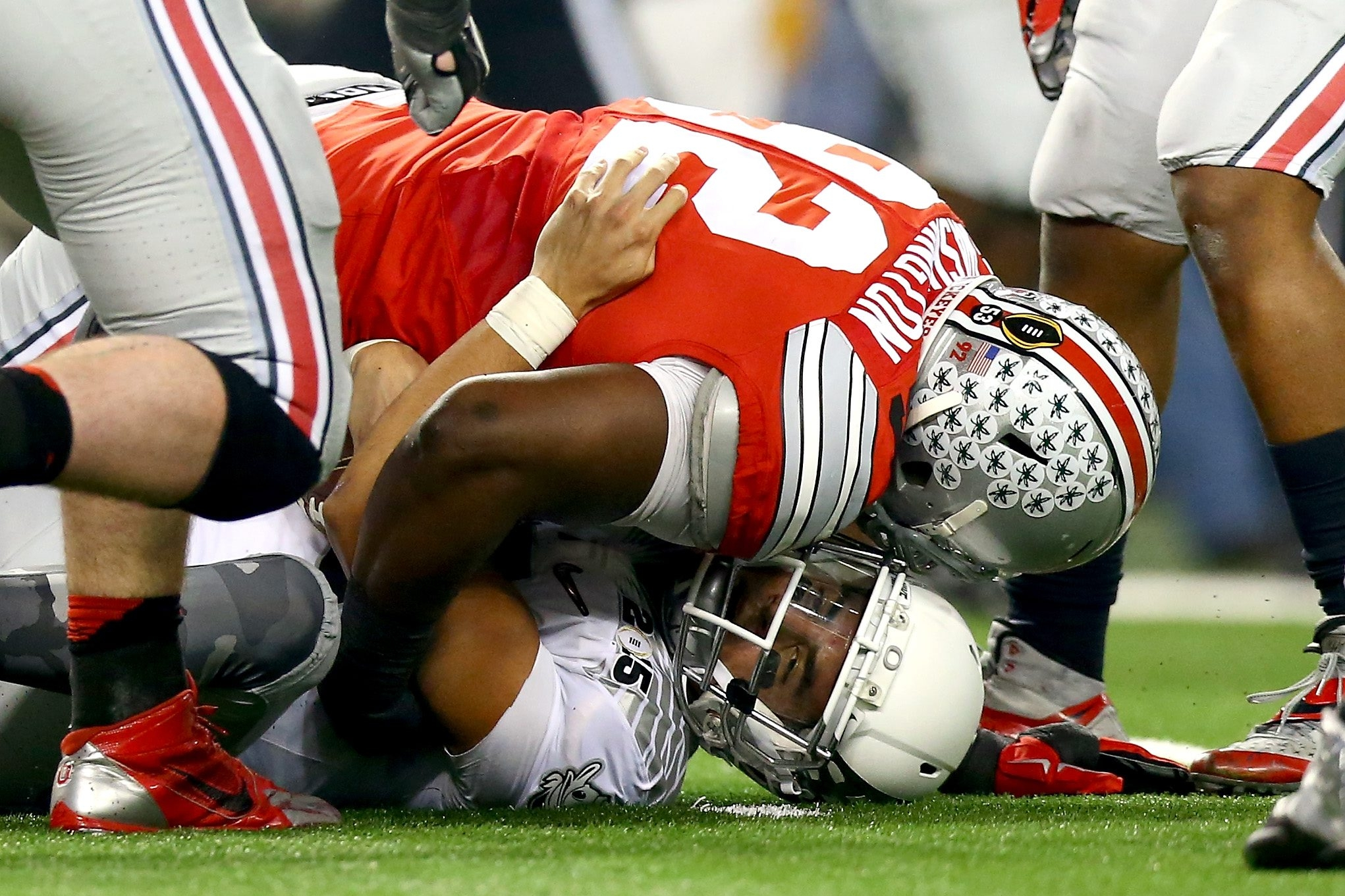 ARLINGTON, TX - JANUARY 12:  Defensive lineman Adolphus Washington #92 of the Ohio State Buckeyes sacks quarterback Marcus Mariota #8 of the Oregon Ducks in the second quarter during the College Football Playoff National Championship Game at AT&T Stadium on January 12, 2015 in Arlington, Texas.  (Photo by Ronald Martinez/Getty Images)