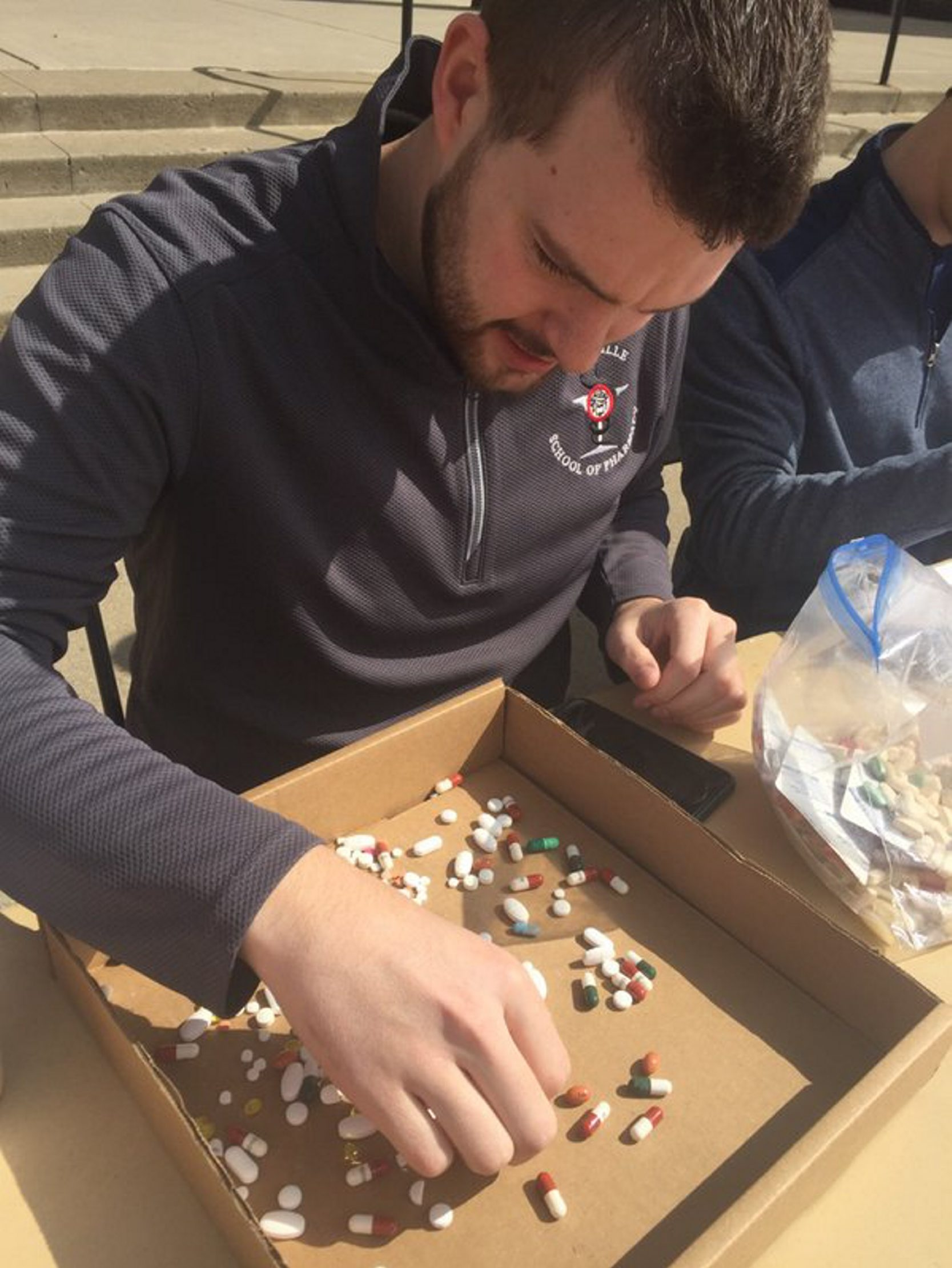 A volunteer identifies drugs turned in at prescription drug dropoff site at SUNY Buffalo State College Saturday. (John Hickey/Buffalo News)