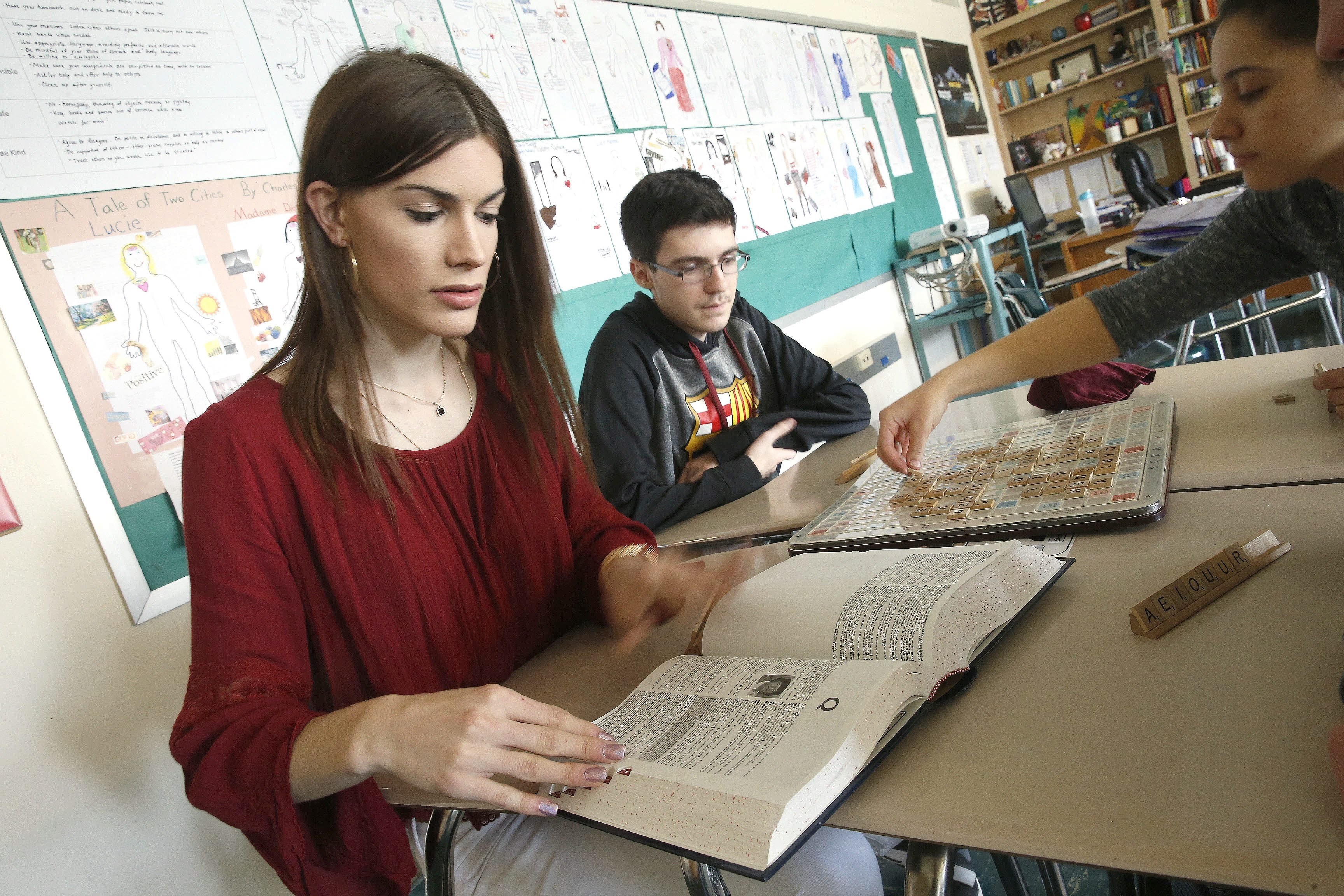 Cheektowaga Central High School sophomore DJ Morley, left, plays a team word board game in her ELA class as classmate Jacob Curr waits for her to look up a word in the dictionary. (Robert Kirkham/Buffalo News)