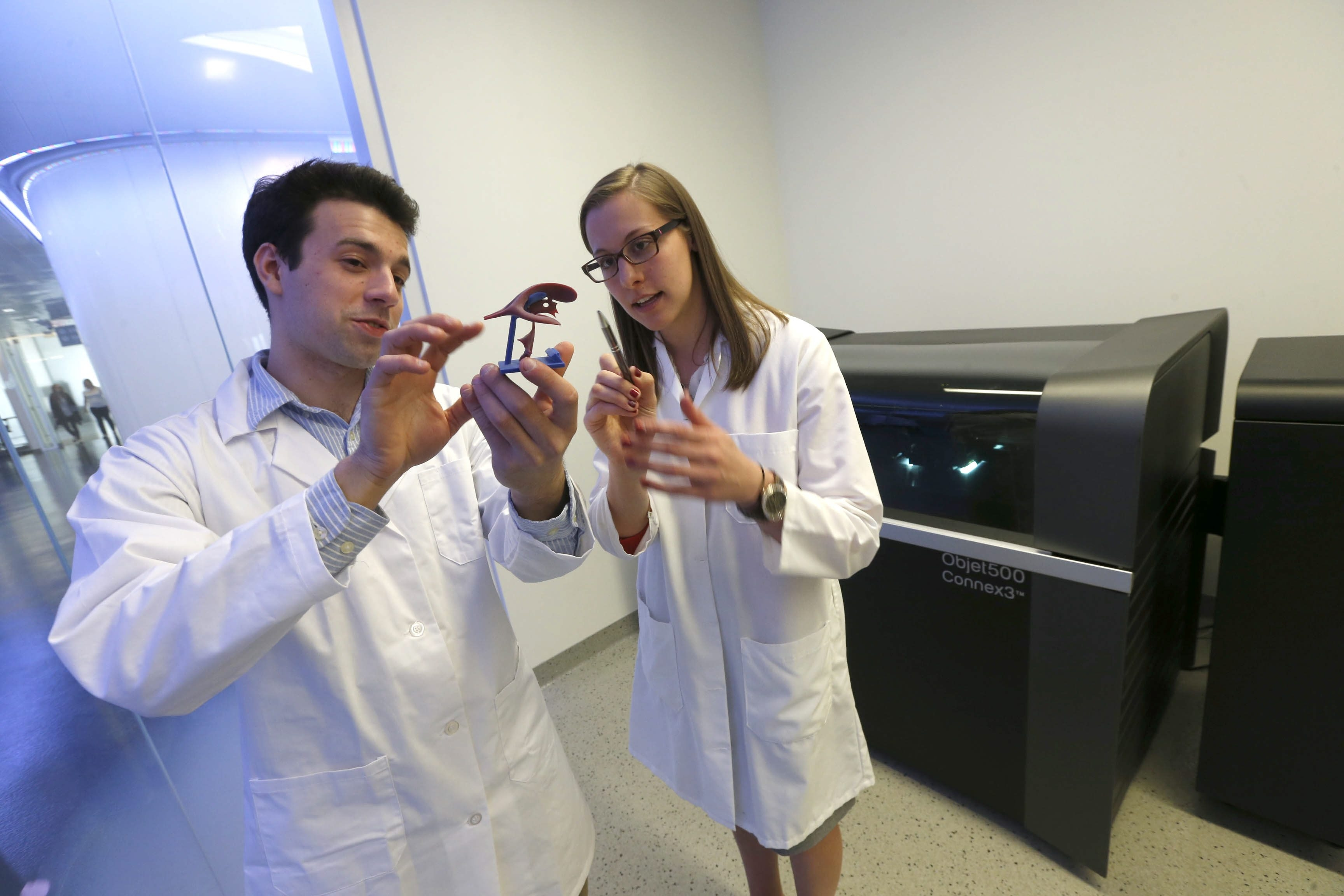 Richard Izzo, a UB graduate student, and Karen Meess, a Jacobs Institute biomedical engineer, discuss a printed 3D model of part of a brain.
