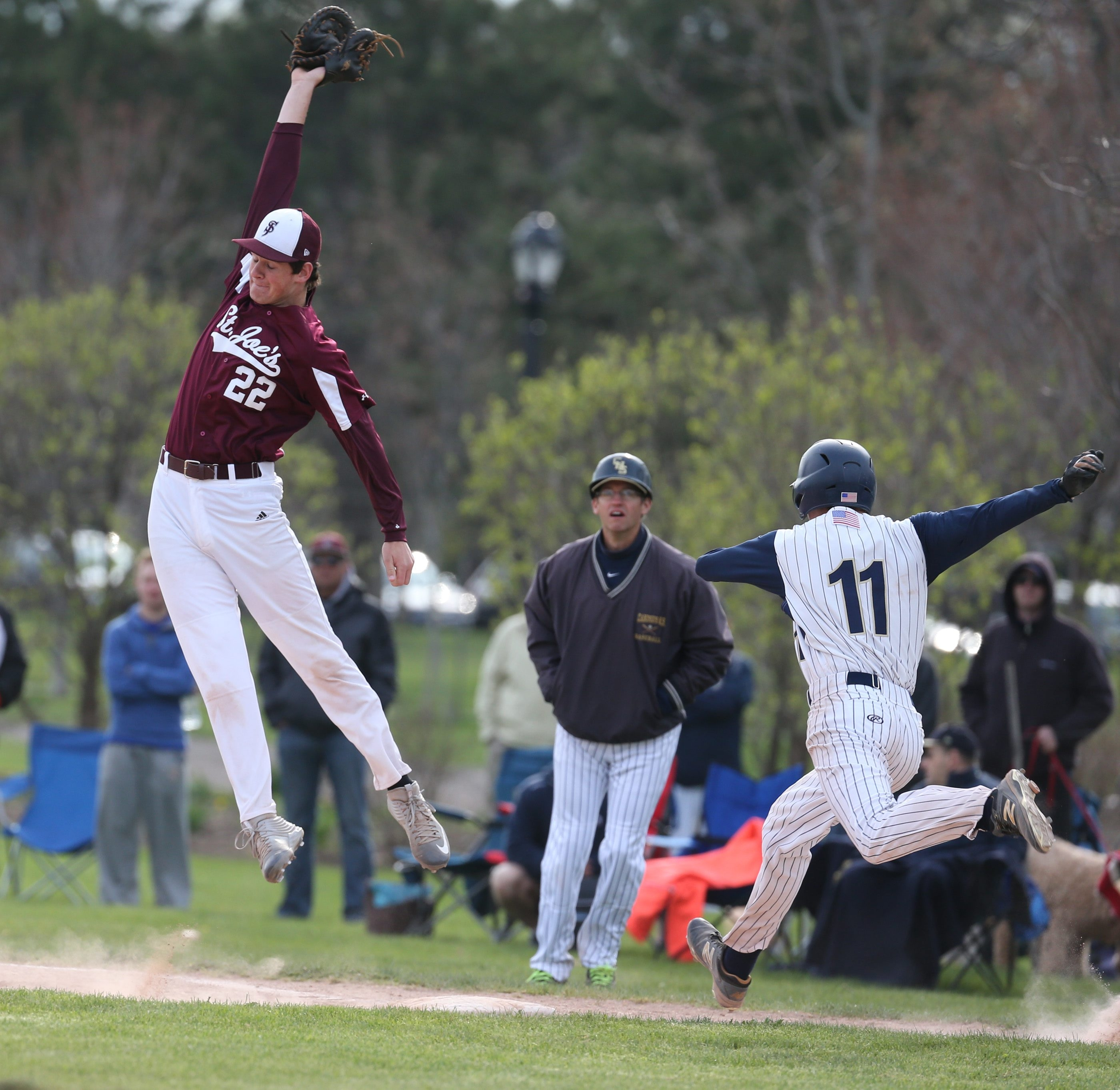 Michael Gabriele (11) of Canisius beat out an infield single as St. Joe's first baseman Anthony Brophy leaps for the high throw in the fifth inning of Monday's game at Delaware Park.