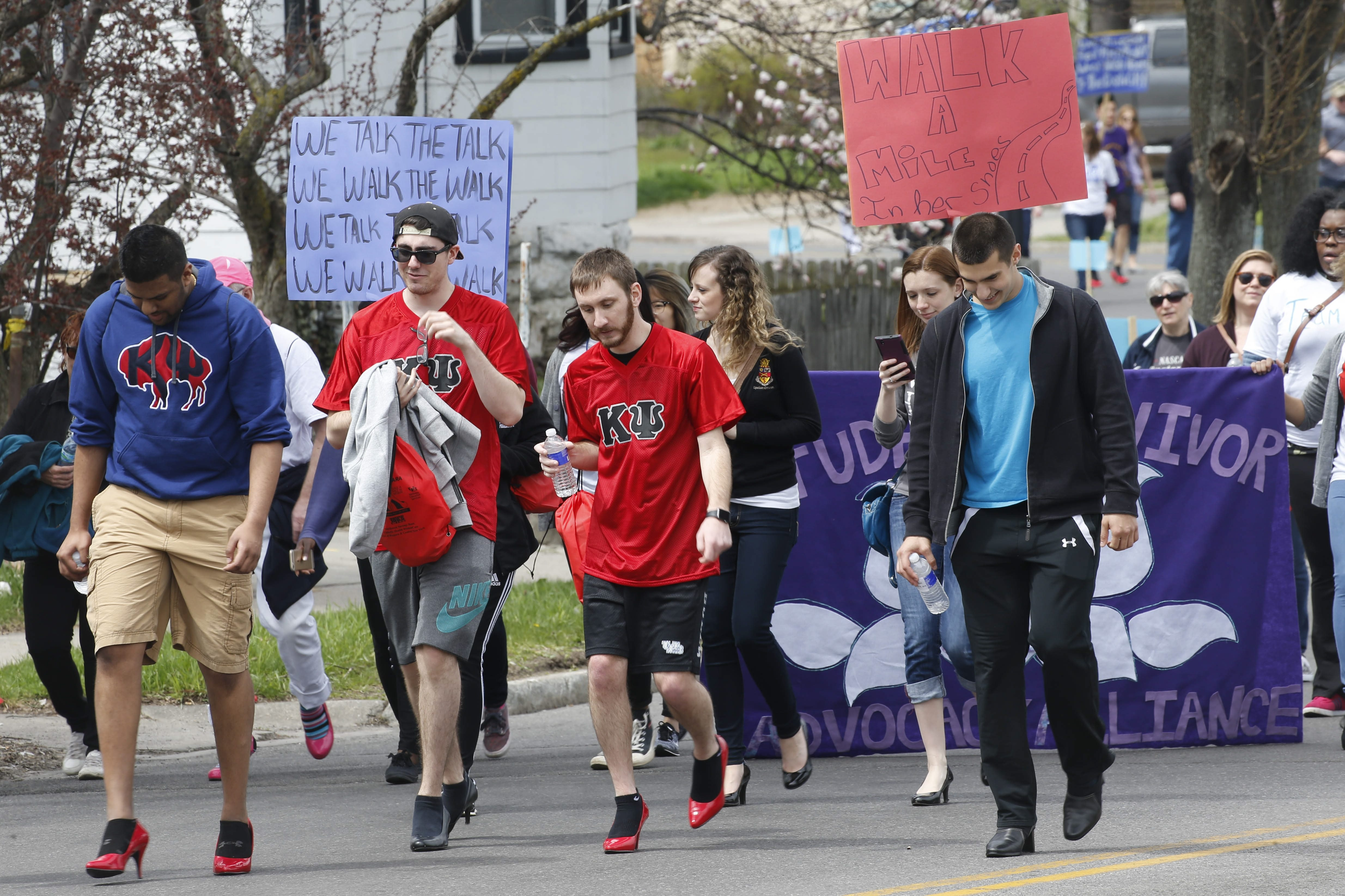 """Derek Gee/Buffalo News  Male participants wearing high heels leg out their march along Hertel Avenue on Sunday in the 11th annual """"Walk a Mile in Her Shoes"""" event, a benefit for Crisis Services, which assists rape victims."""
