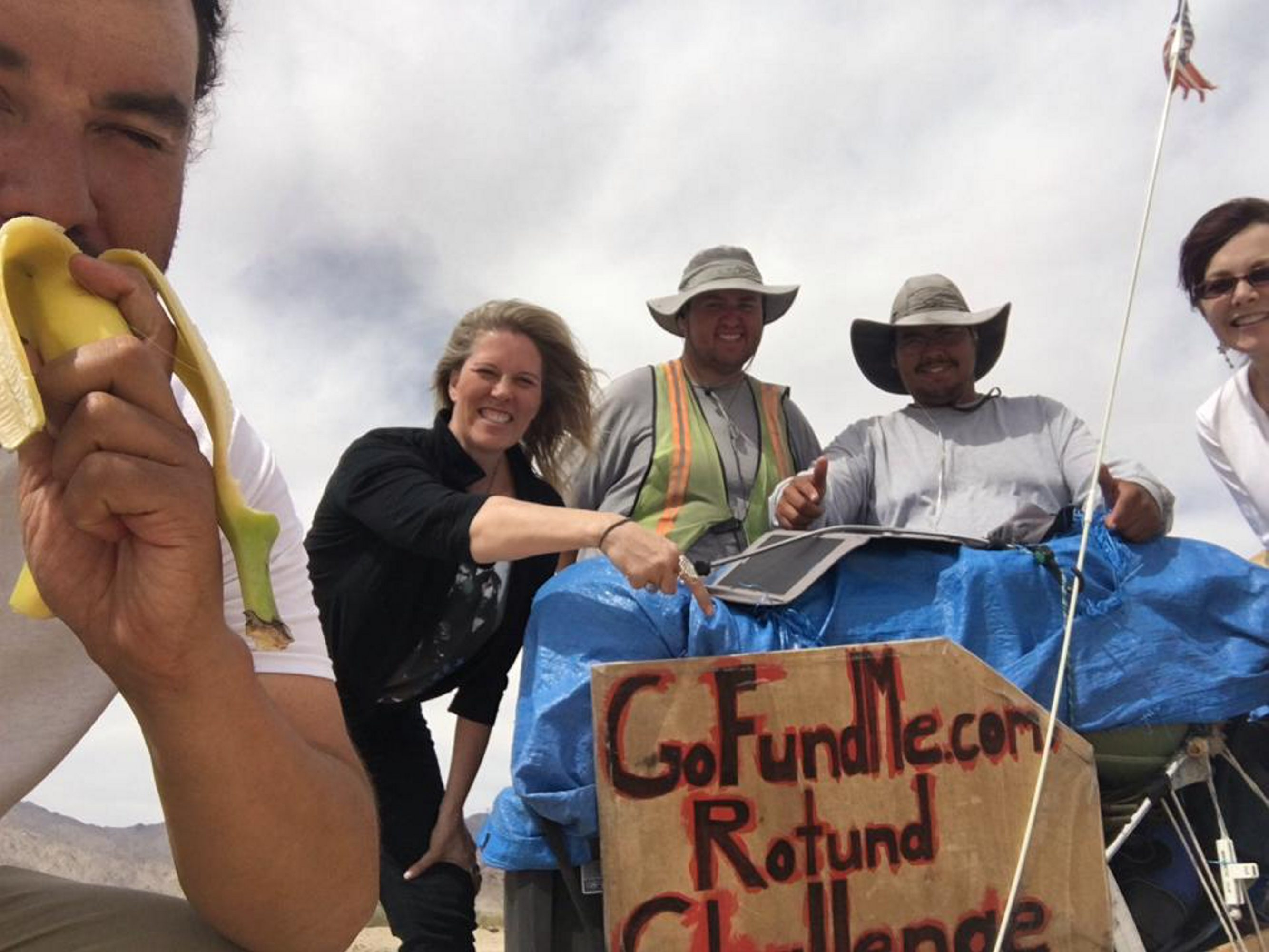 Joe Cooke, left, dug into a banana while Jason Rogers, center, and Chris Cooke, pose for a photo with Lisa Sievenpiper Davis, second from left, and her friend Eden Maureen Becket, who brought food and water to the three walkers. (File photo)
