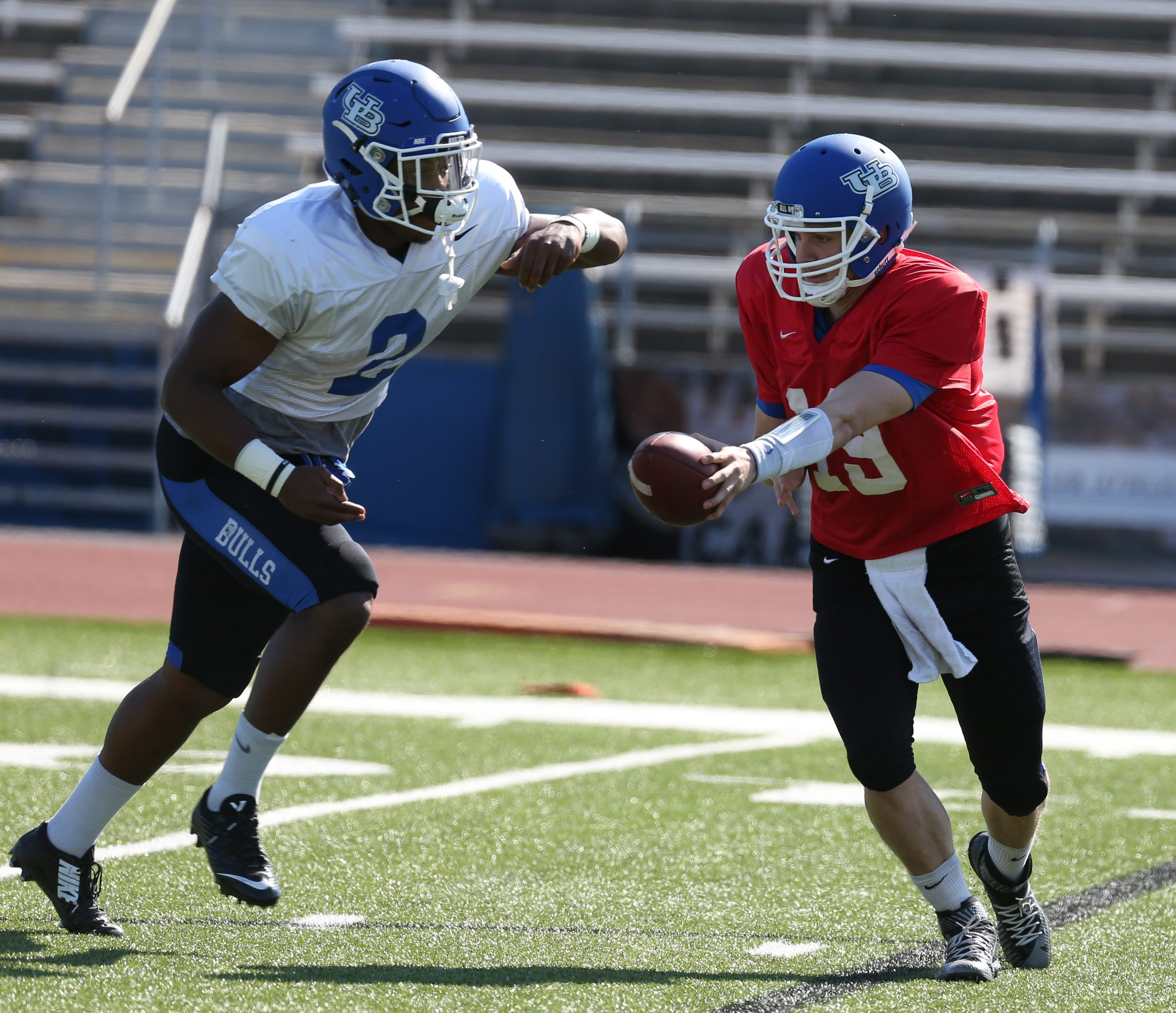 Quarterback Grant Rohach hands off  to Jordan Johnson during individual drills before Saturday's UB scrimmage at UB Stadium. Johnson sat out the scrimmage with a minor injury. (James P. McCoy/Buffalo News)