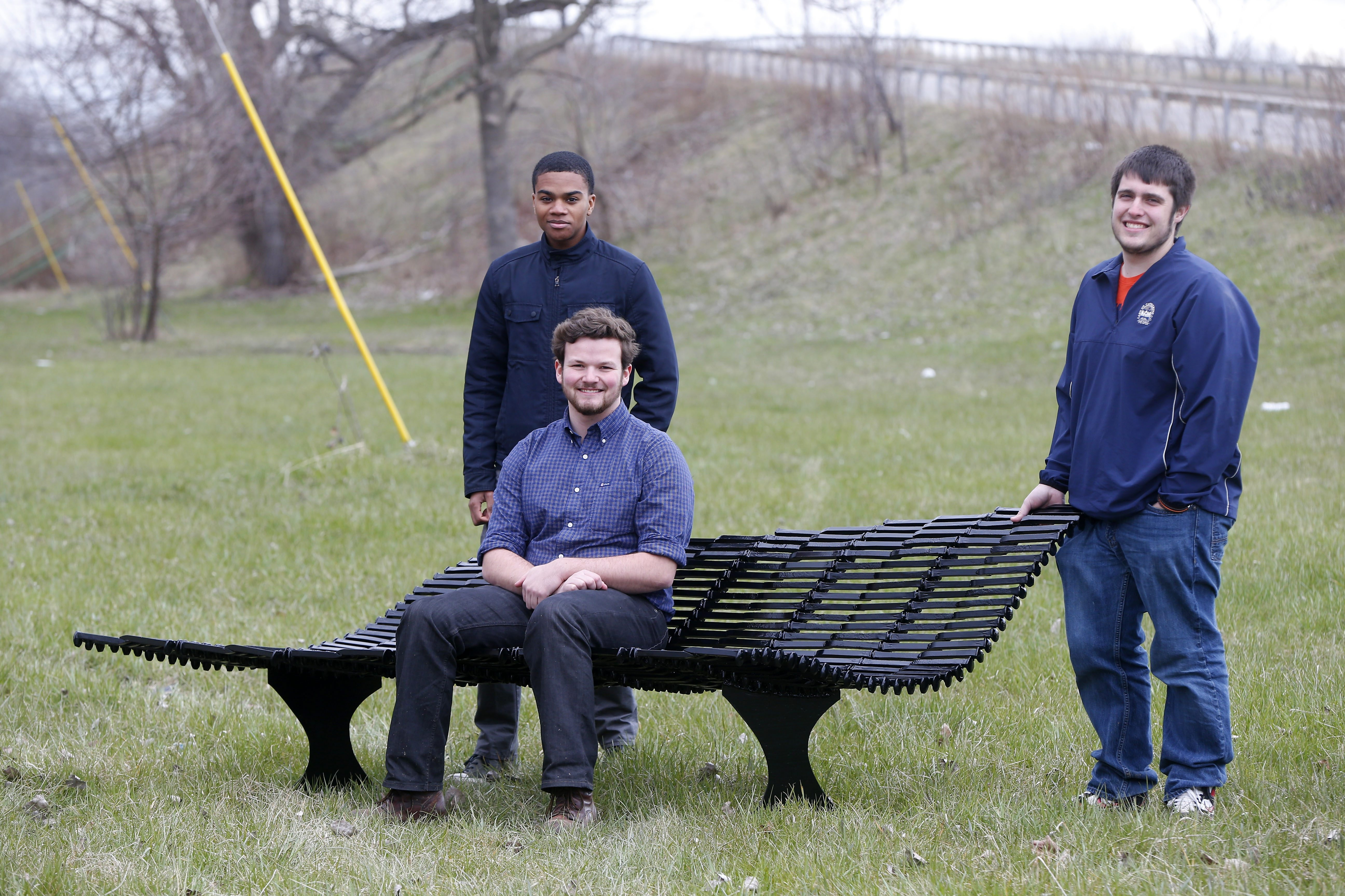 Students from UB's School of Architecture and Planning – from left, Stephon-Rae Jackson, Dylan Burns and Garrett Brown – offer a look at the bench created from 438 rail spikes to reflect the history and culture of the Old First Ward as part of community project.