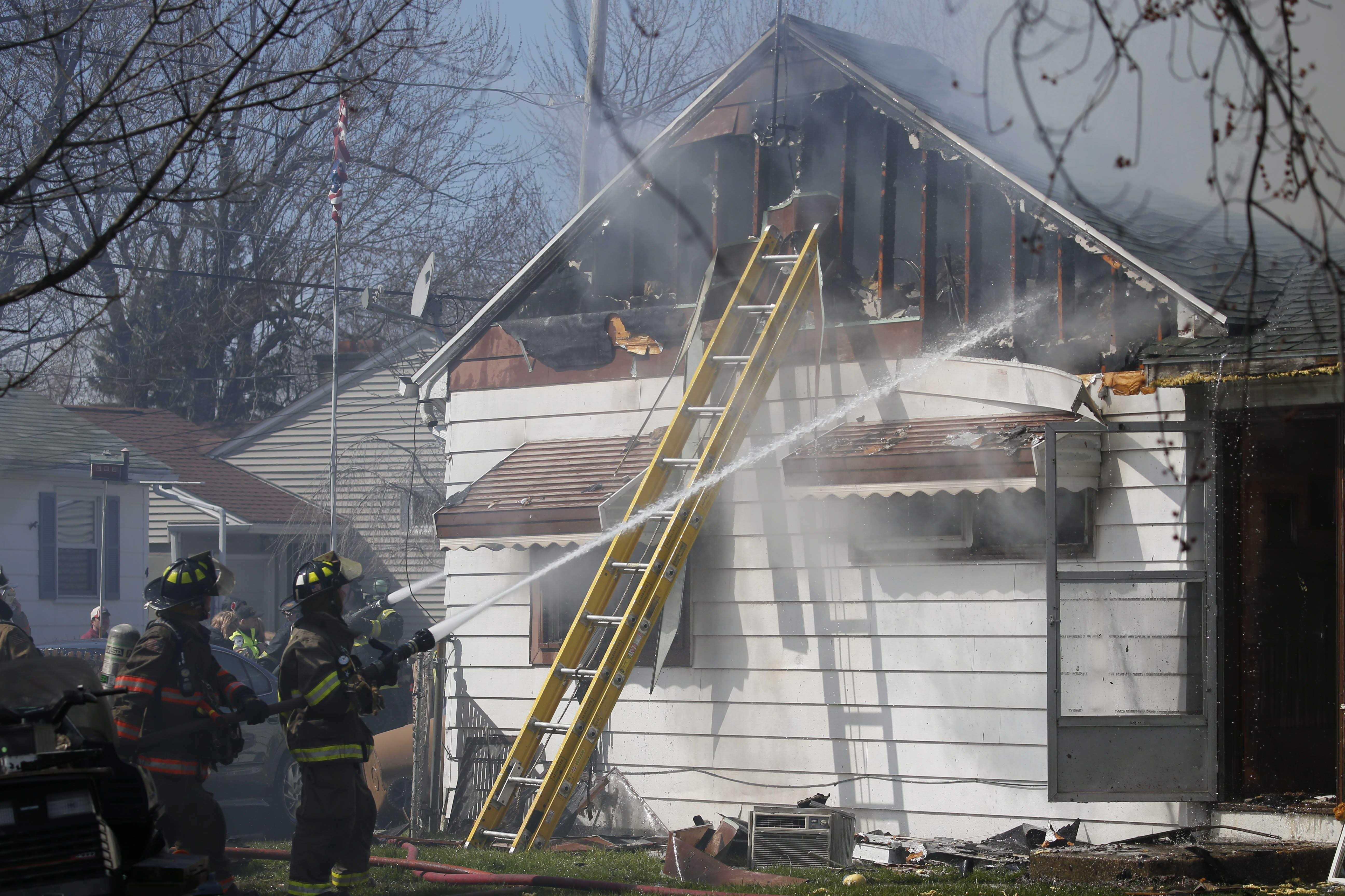 Firefighters work to contain a fire in an occupied home on Brookhaven Drive in Cheektowaga on Saturday, April 9, 2016.  (Derek Gee/Buffalo News)