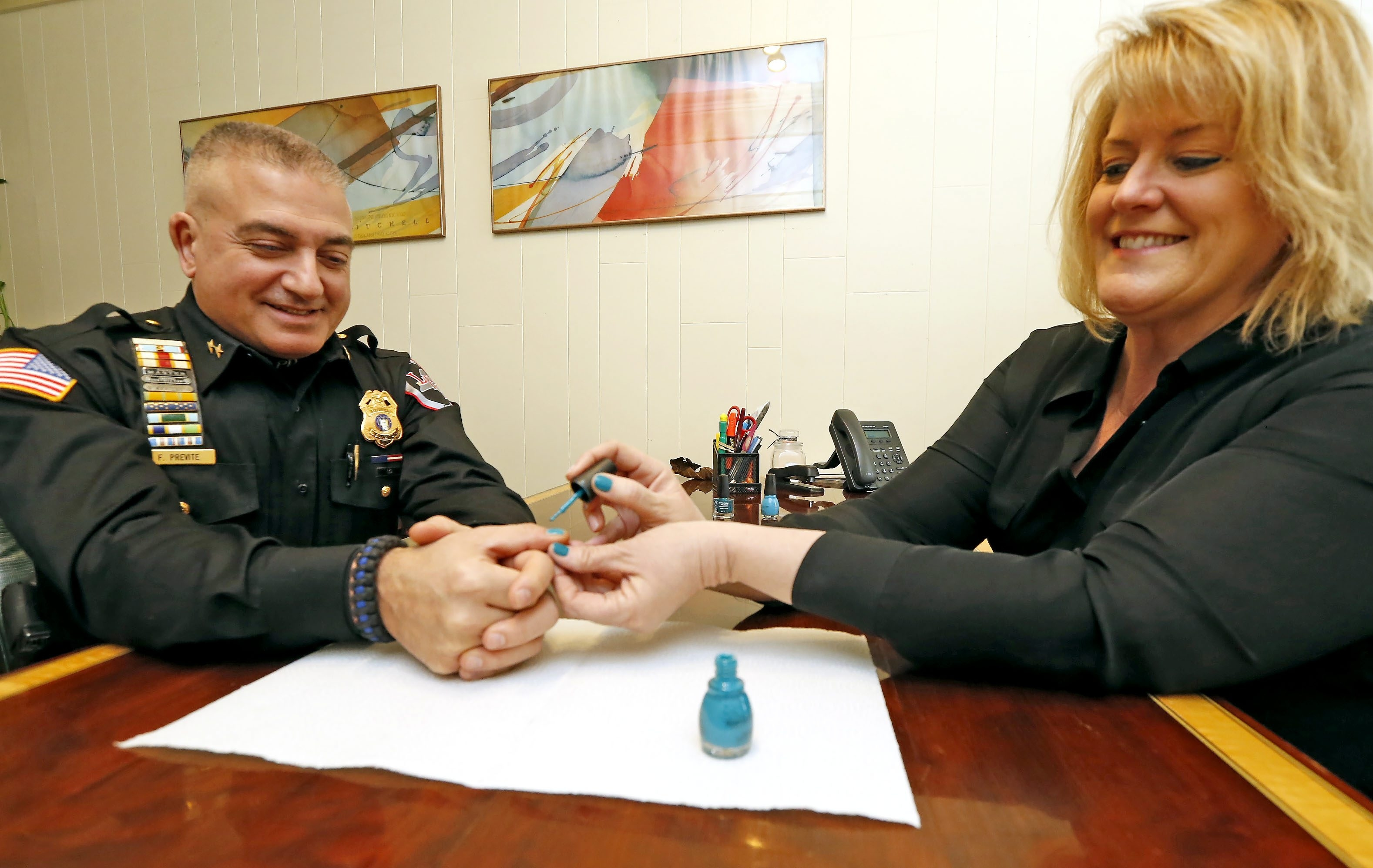 """Sandra Lahrache, acting executive director of """"It Happened to Alexa Foundation,"""" right, paints Lewiston Police Chief Frank Previte's thumbnails as part of the Painting the Town Teal campaign last week."""