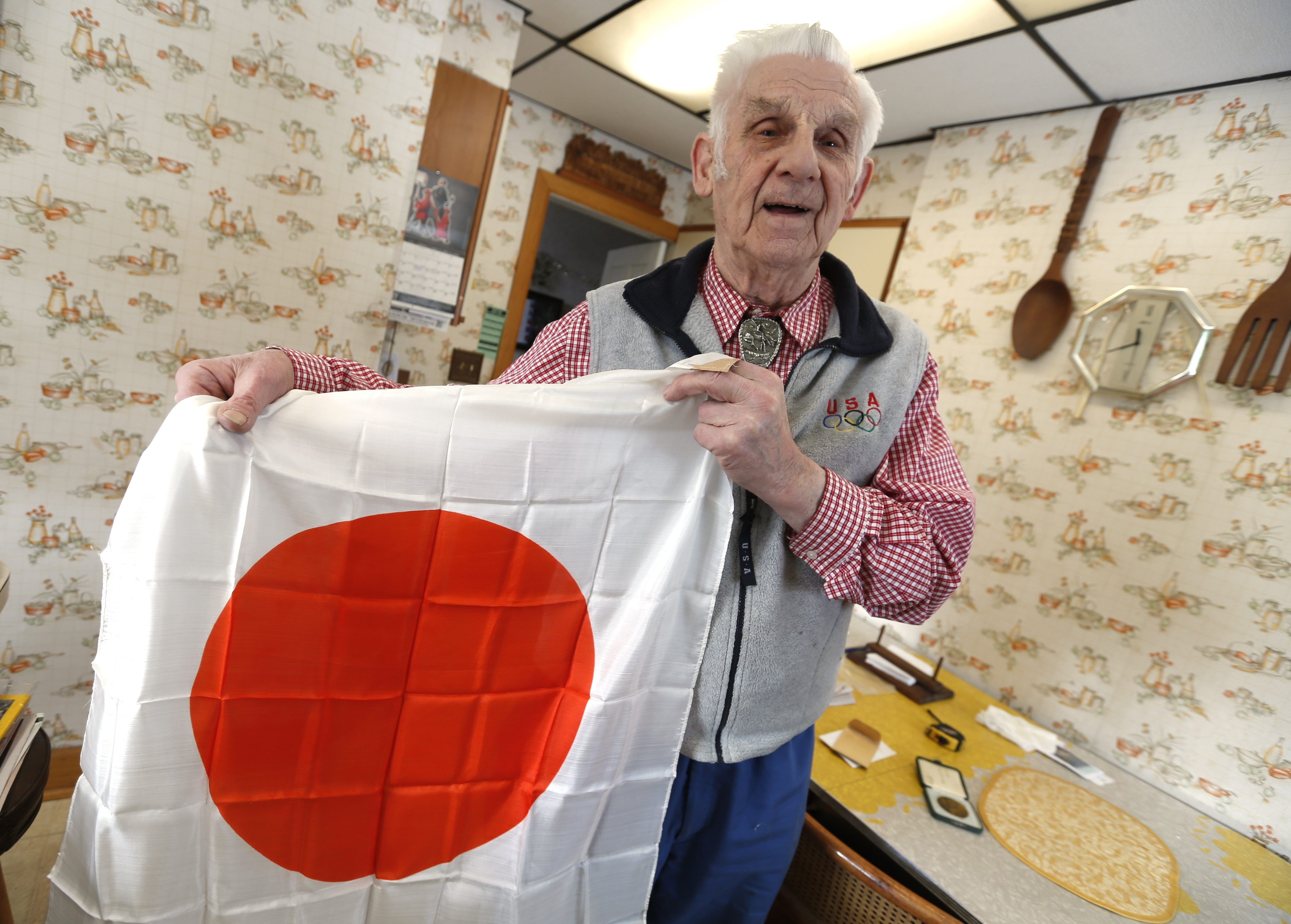 A Japanese flag is among Louis J. Lambert's mementos in his East Aurora home. He also recalls bartering ciga- rettes for a sword, which got lost, and a couple of rifles.