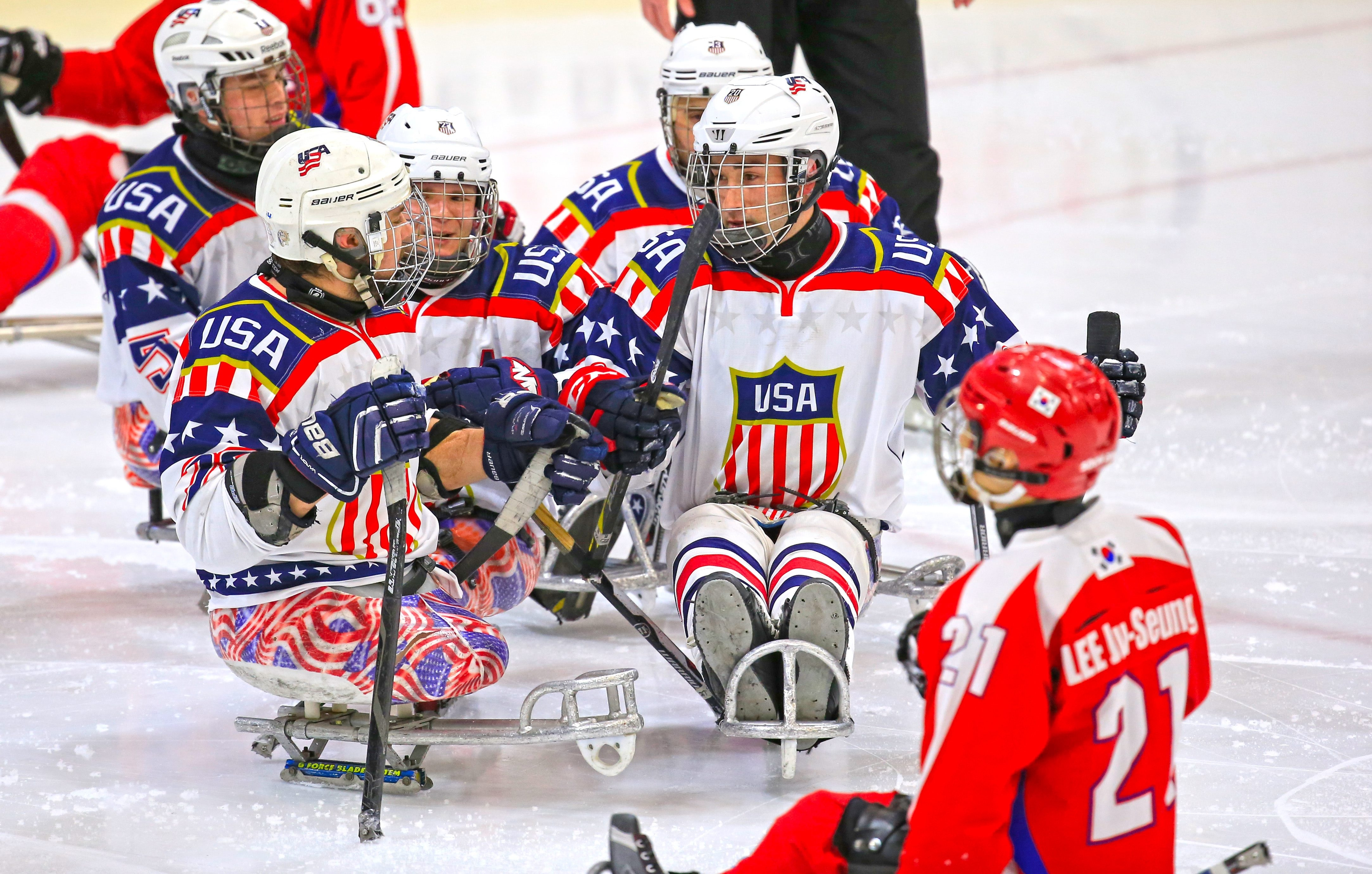 Team USA's Adam Page, right, celebrates his first goal of the game with Paul Schaus, front left, during the second period of a win over Korea.