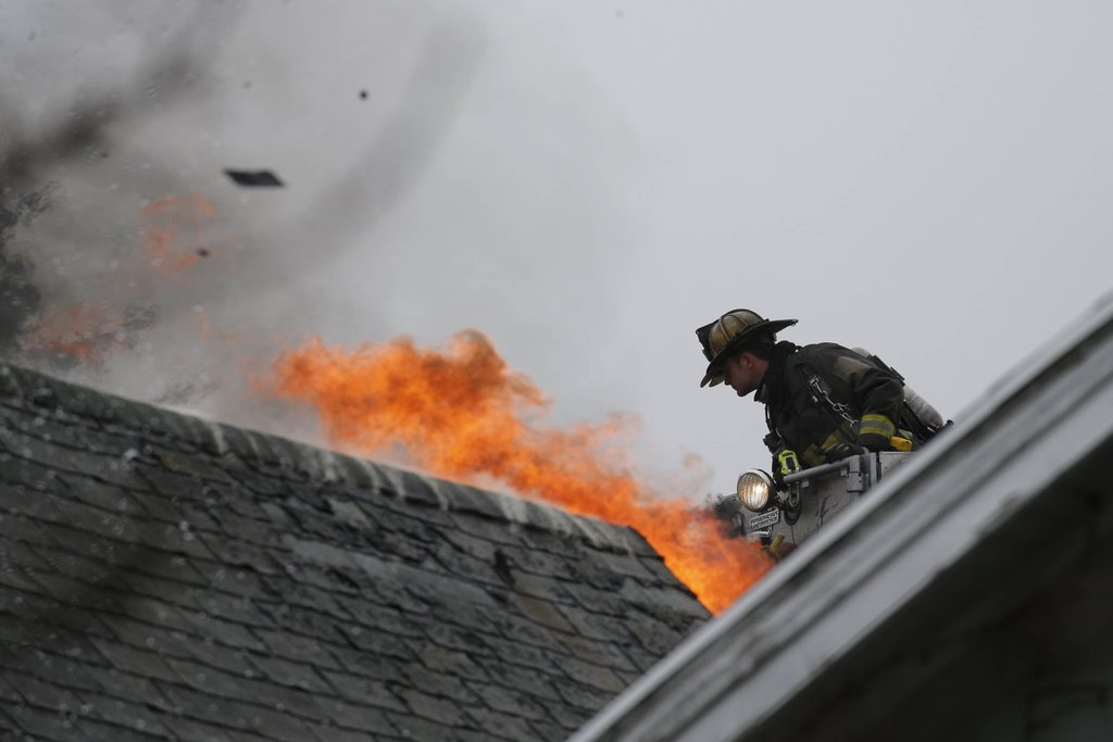 Flames rise from the roof of 11 Remoleno St. as a Buffalo firefighter in a ladder truck works from a distance. (Derek Gee/Buffalo News)
