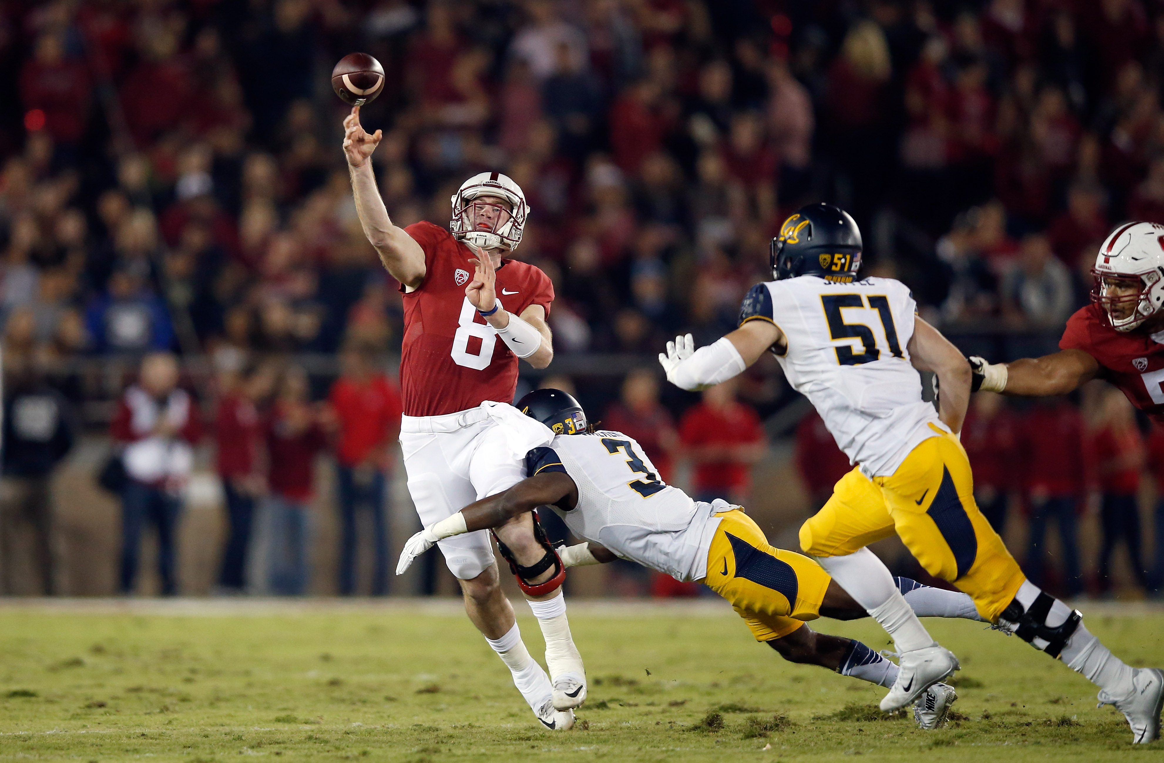 PALO ALTO, CA - NOVEMBER 21:  Kevin Hogan #8 of the Stanford Cardinal is hit by Cameron Walker #3 of the California Golden Bears as he throws the ball at Stanford Stadium on November 21, 2015 in Palo Alto, California.  (Photo by Ezra Shaw/Getty Images)