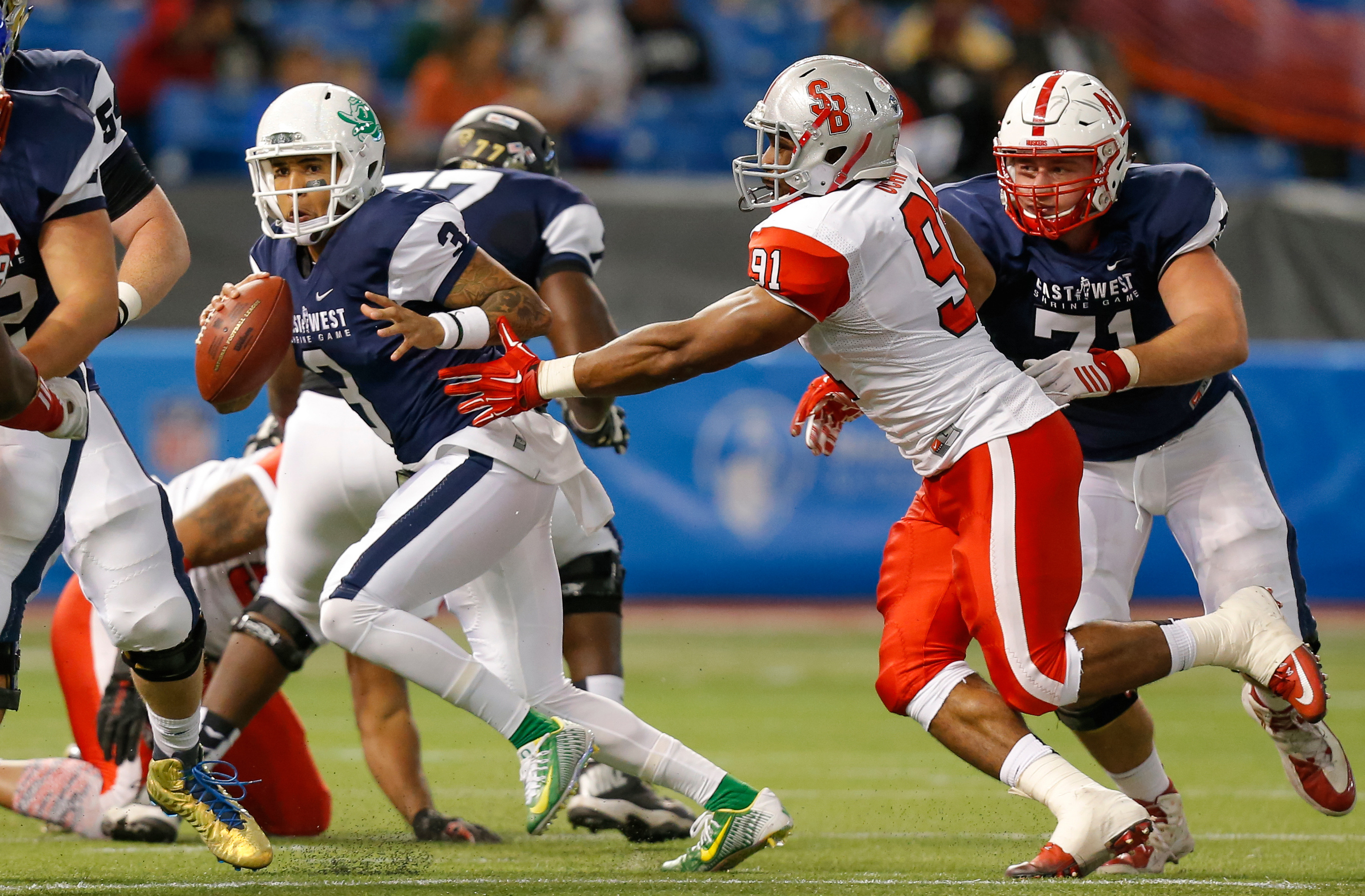 ST. PETERSBURG, FL - JANUARY 23:  Vernon Adams Jr. #3 from Oregon playing on the West Team avoids a tackle from Victor Ochi #91 from Stony Brook playing on the East Team during the first half of the East West Shrine Game at Tropicana Field on January 23, 2016 in St. Petersburg, Florida. (Photo by Mike Carlson/Getty Images)