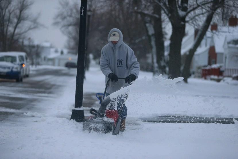 Jim Morrison snowblows his neighbor's sidewalks this morning on Truesdale Road in Town of Tonawanda. (John Hickey/Buffalo News)