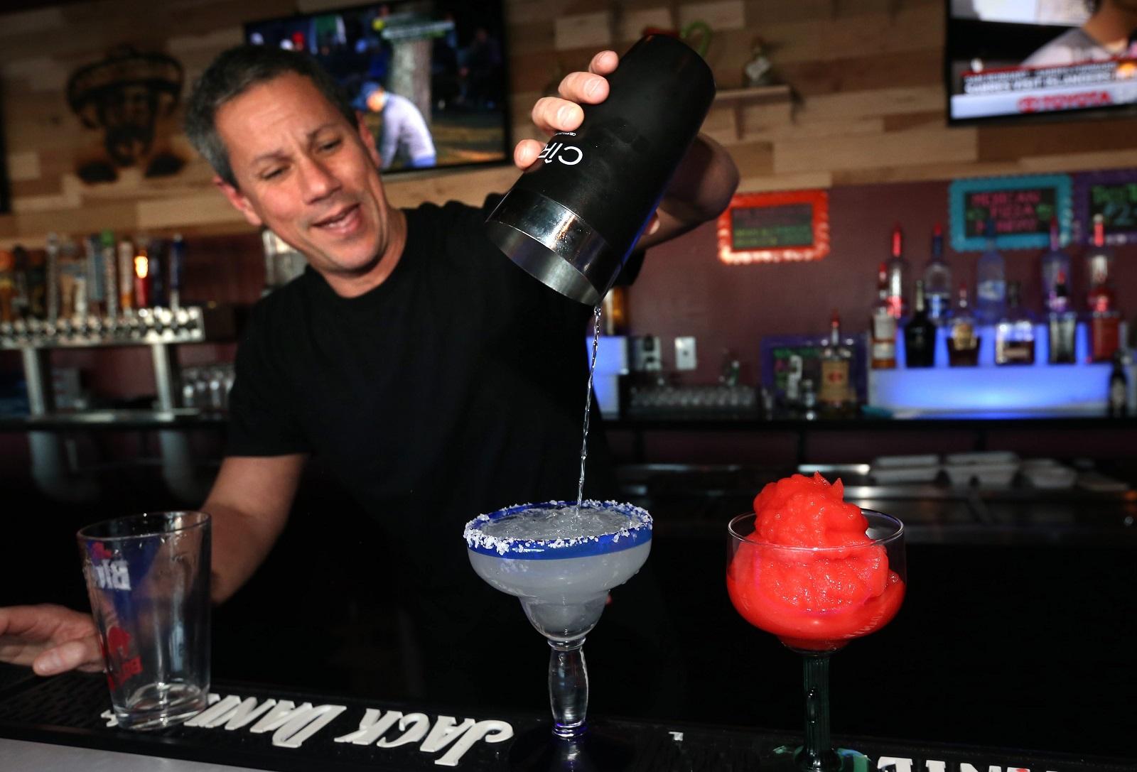 Papi Grande's bartender Hector Enrique Mondul makes a traditional margarita and a strawberry margarita. (Sharon Cantillon/Buffalo News)