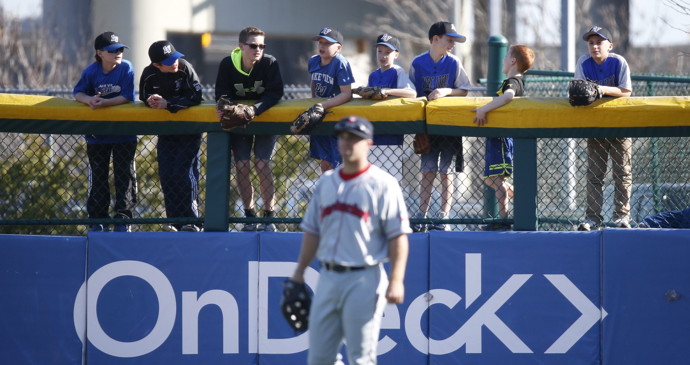 Buffalo Bisons fans hang over the right field fence to watch action against the Pawtucket Red Sox earlier this season. (Harry Scull Jr./Buffalo News)