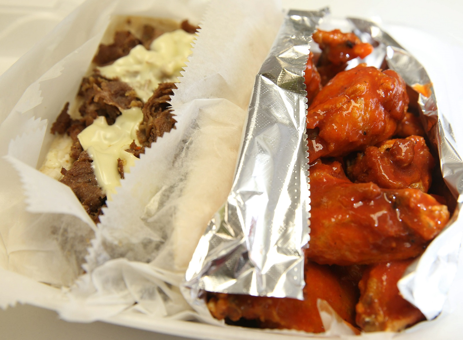 Medium wings, right, sit next to a Philly cheesesteak from DJ Cafeteria. (Sharon Cantillon/Buffalo News)