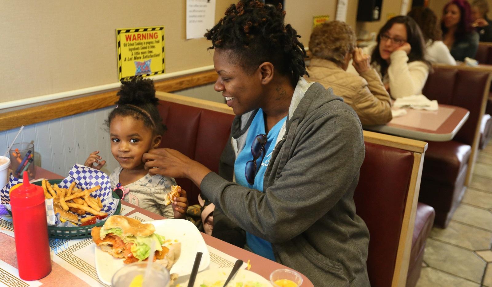 Tiffani Wofford, of Buffalo, eats lunch at Greek to Me with her daughter Song Alexander, 2. (Sharon Cantillon/Buffalo News)