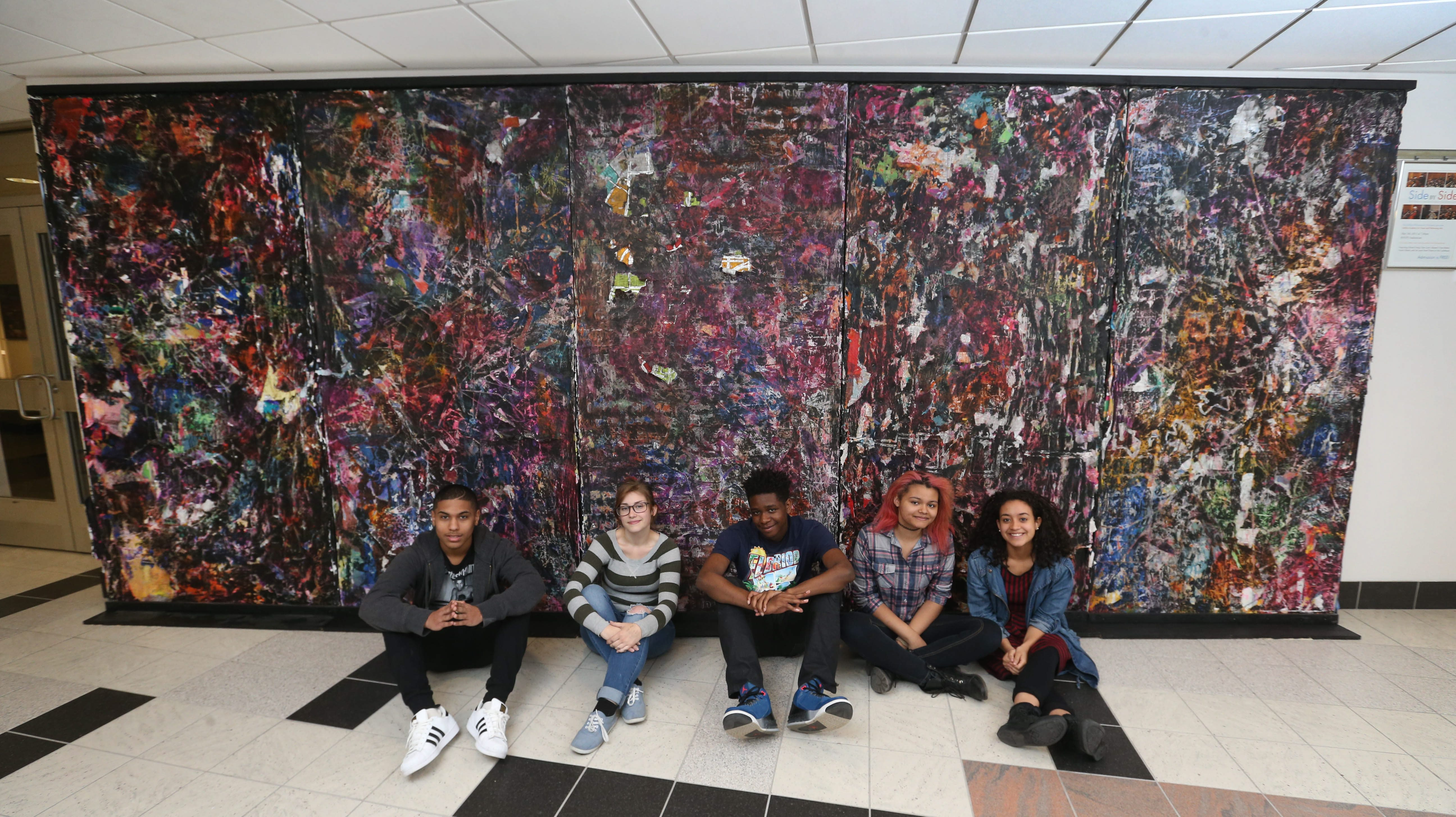 Students at Buffalo Academy for Visual and Performing Arts completed a project inspired by artist Mark Bradford who has a show opening at the Albright-Knox Art Gallery this week.  Angel Galarza, left, Carolyn Zimpfer, Benjamin Pierce, Paige Reed and Sara Jaime are five of the students who created the piece.  Several more worked on it as well. The the large scale painting 'Five Buffalos' is made from layers of collage and then sanded to reveal what's in the layers.  Though abstract, students did extensive research about the city.  It consists of five different panels expressing different aspects of Buffalo which include quality of life, environmental, where we live, history and hope/ future.  Photo taken,Friday, May 20, 2016.  (Sharon Cantillon/Buffalo News)