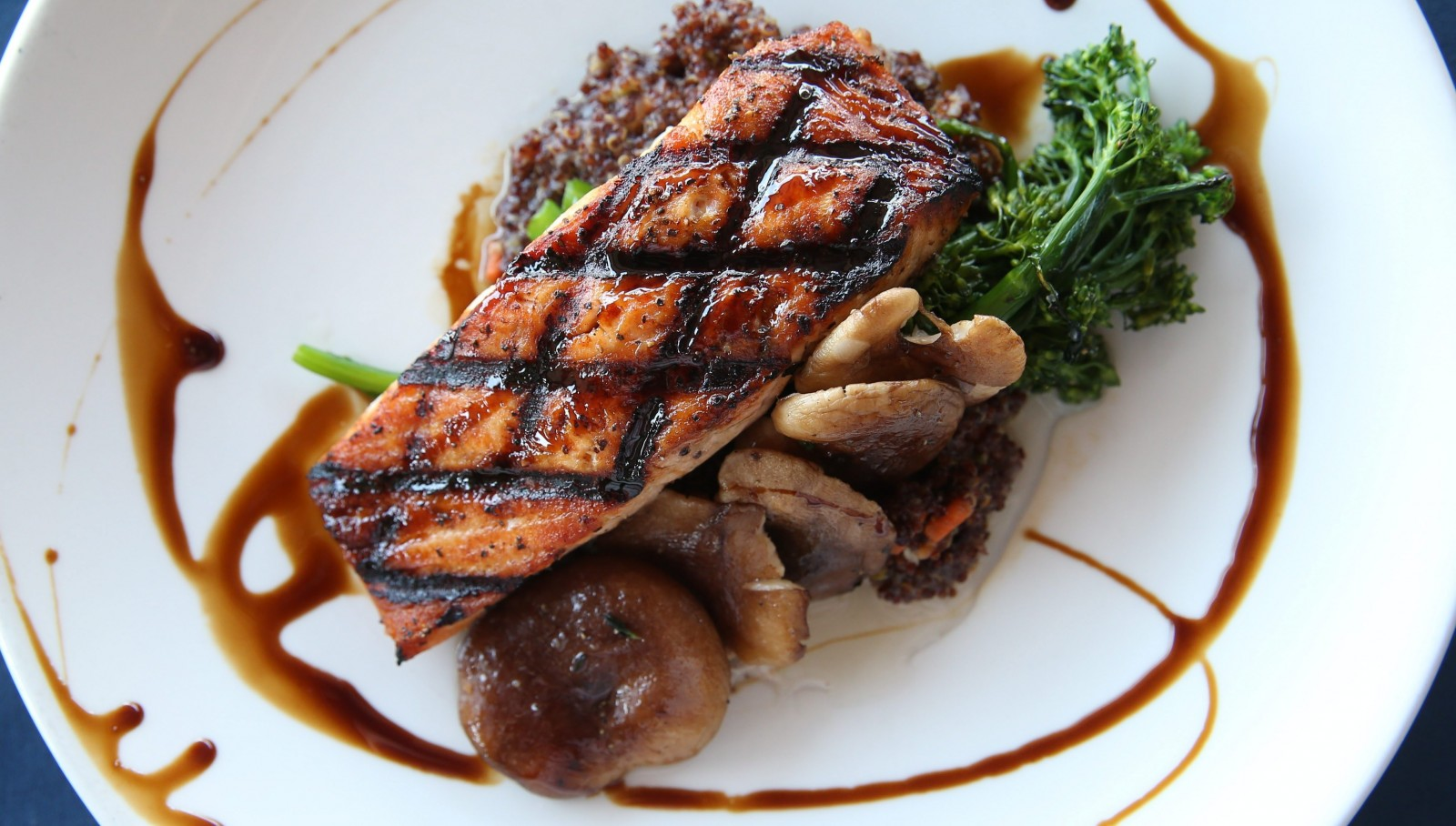 Salmon is grilled and sweet glazed and comes with roasted mushrooms and red quinoa. (Sharon Cantillon/Buffalo News)