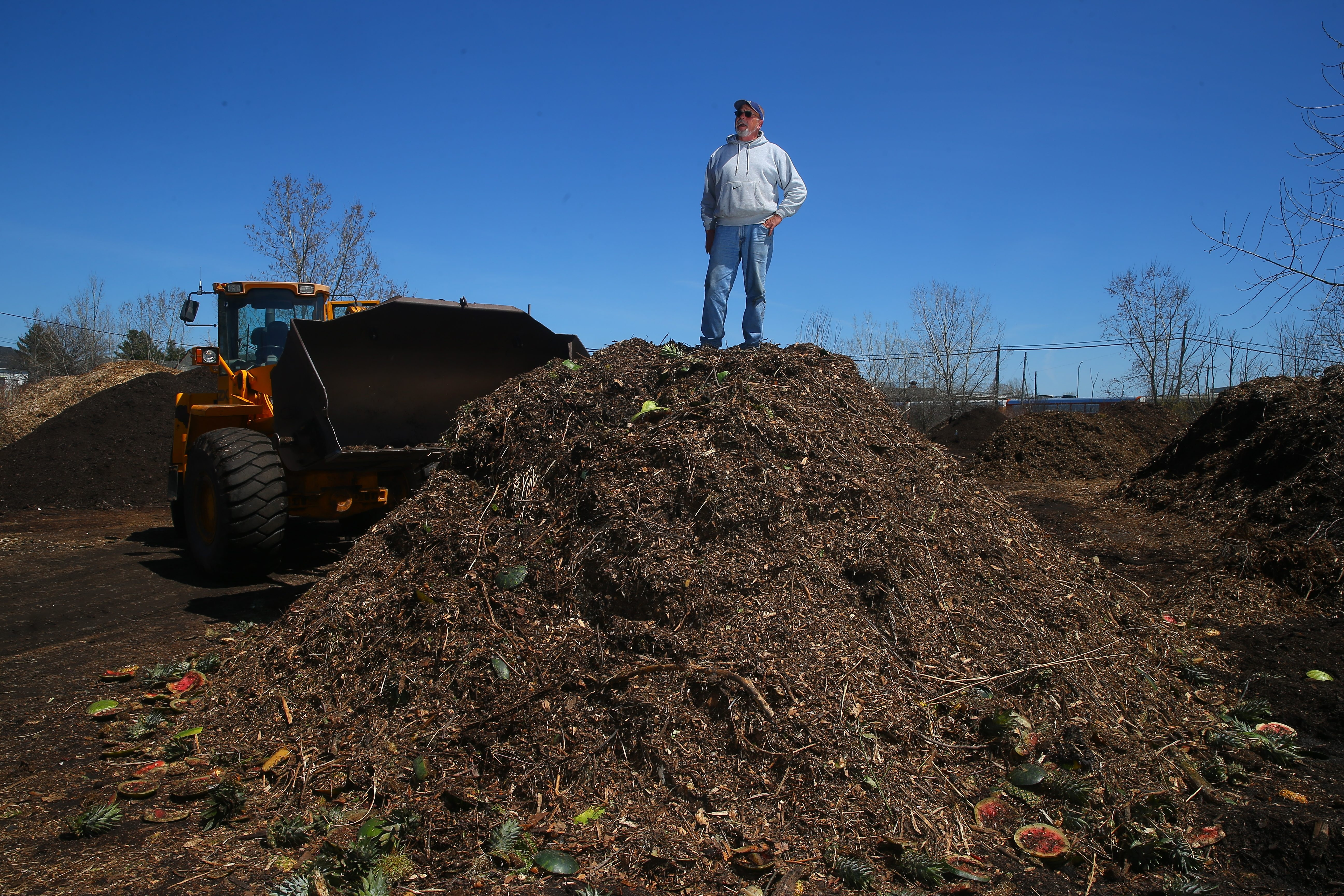 "Dave Majewski  stands Wednesday atop one of the compost piles at his composter site. Majewski takes in about a half-ton of ""organic surplus"" daily from the Buffalo Zoo to reuse as compost."