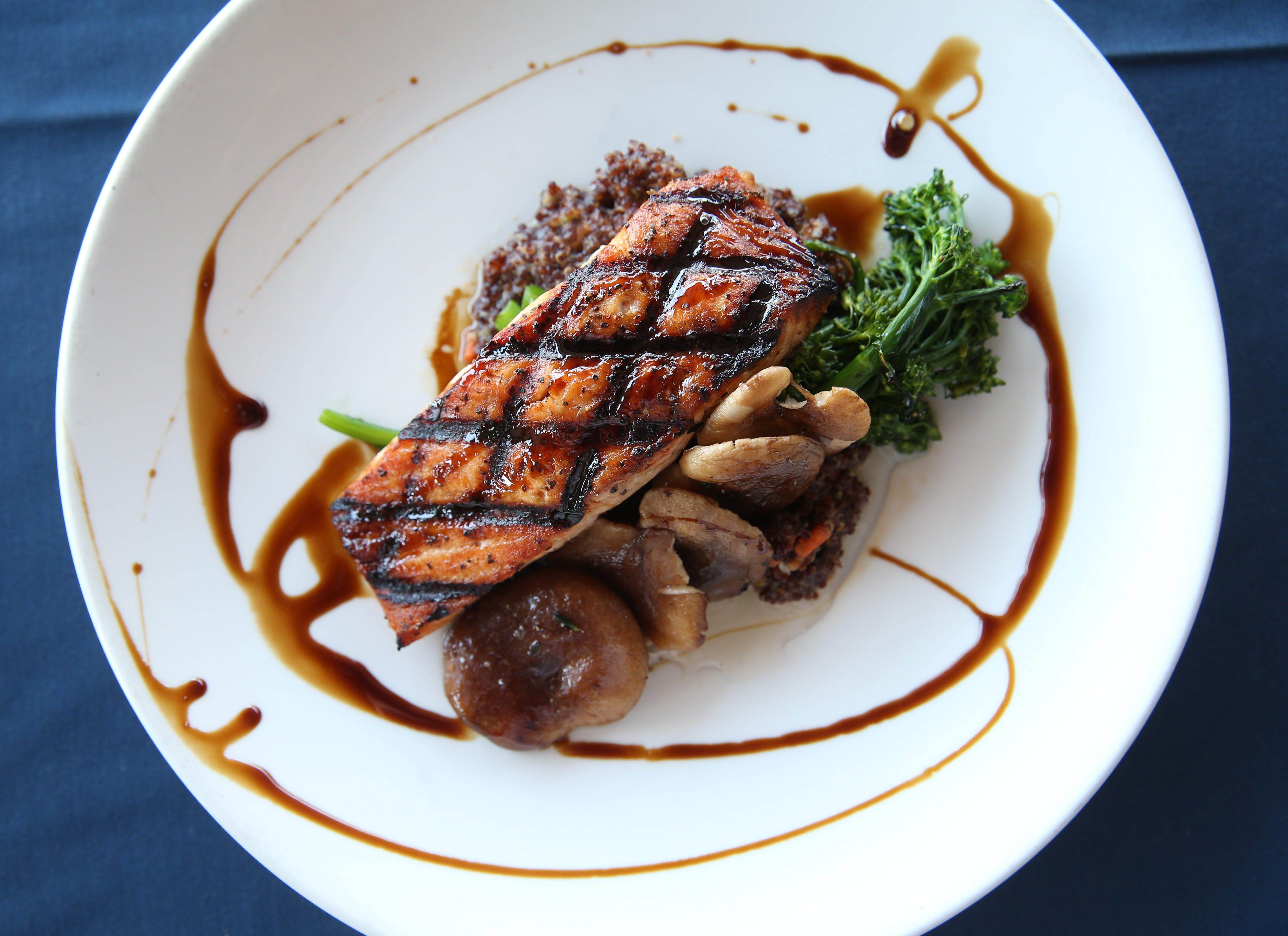 Fish is grilled and sweet glazed and comes with roasted mushrooms and red quinoa.