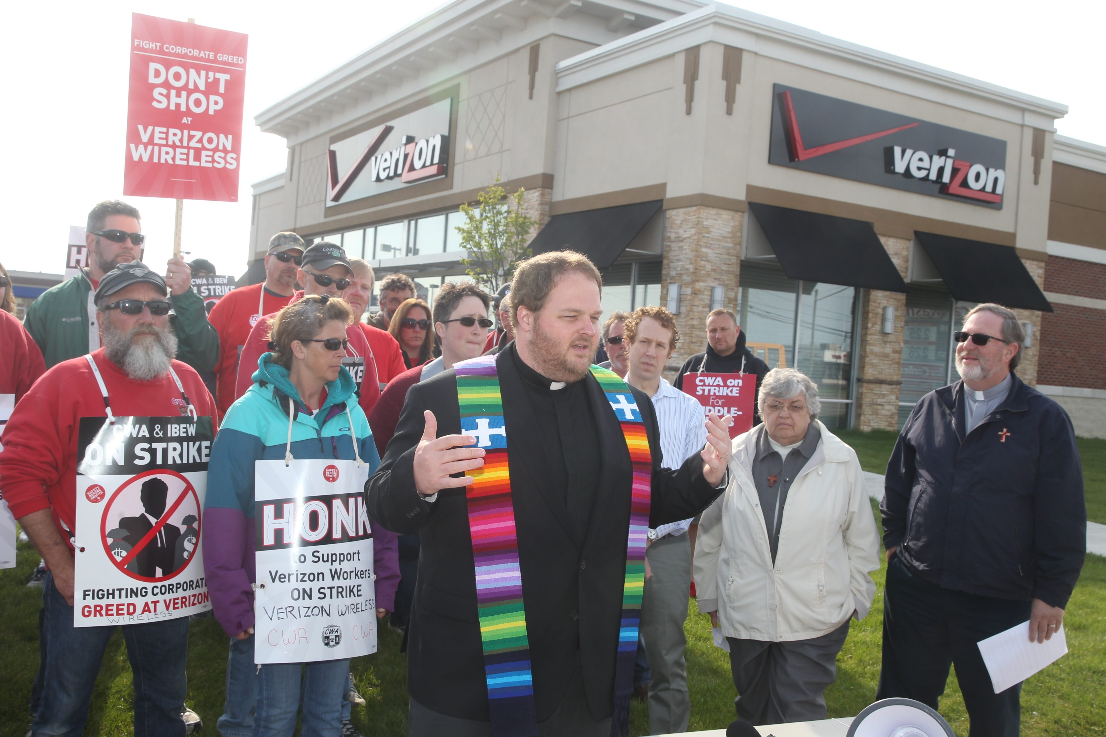 Rev. Kirk Loubenstein, director of the Coalition for Economic Justice, and other members of the clergy join Verizon workers on the strike line after a prayer vigil at the Verizon Wireless store at Union Road and Walden Avenue on Wednesday.