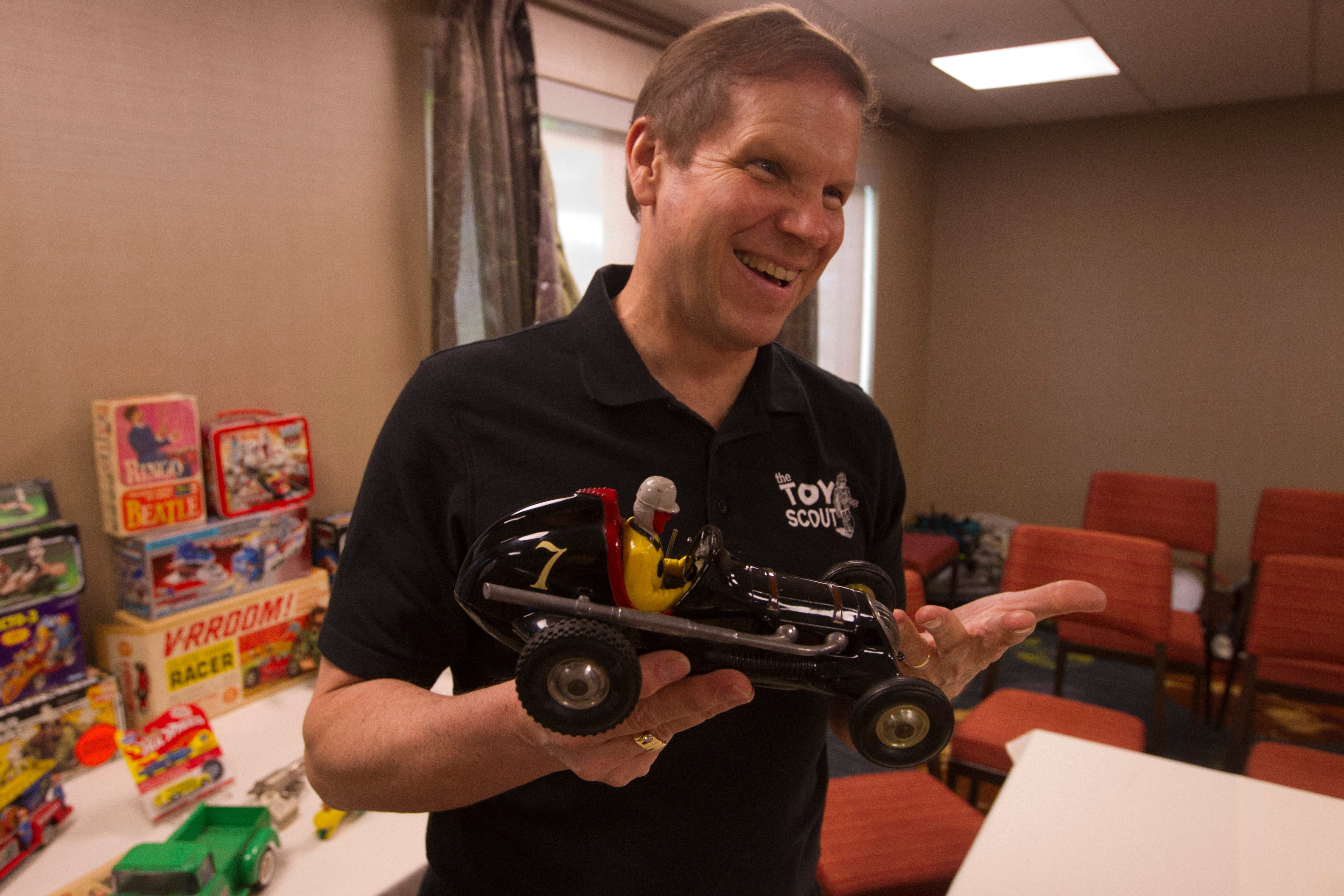 Toy collector and dealer Jerry Magee looks at a Cox Thimble Drome Racer toy from the 1940s at the Courtyard by Marriott in Amherst on Thursday. Magee will be appraising and buying decades-old playthings through the weekend. Other toys brought to him are at right.