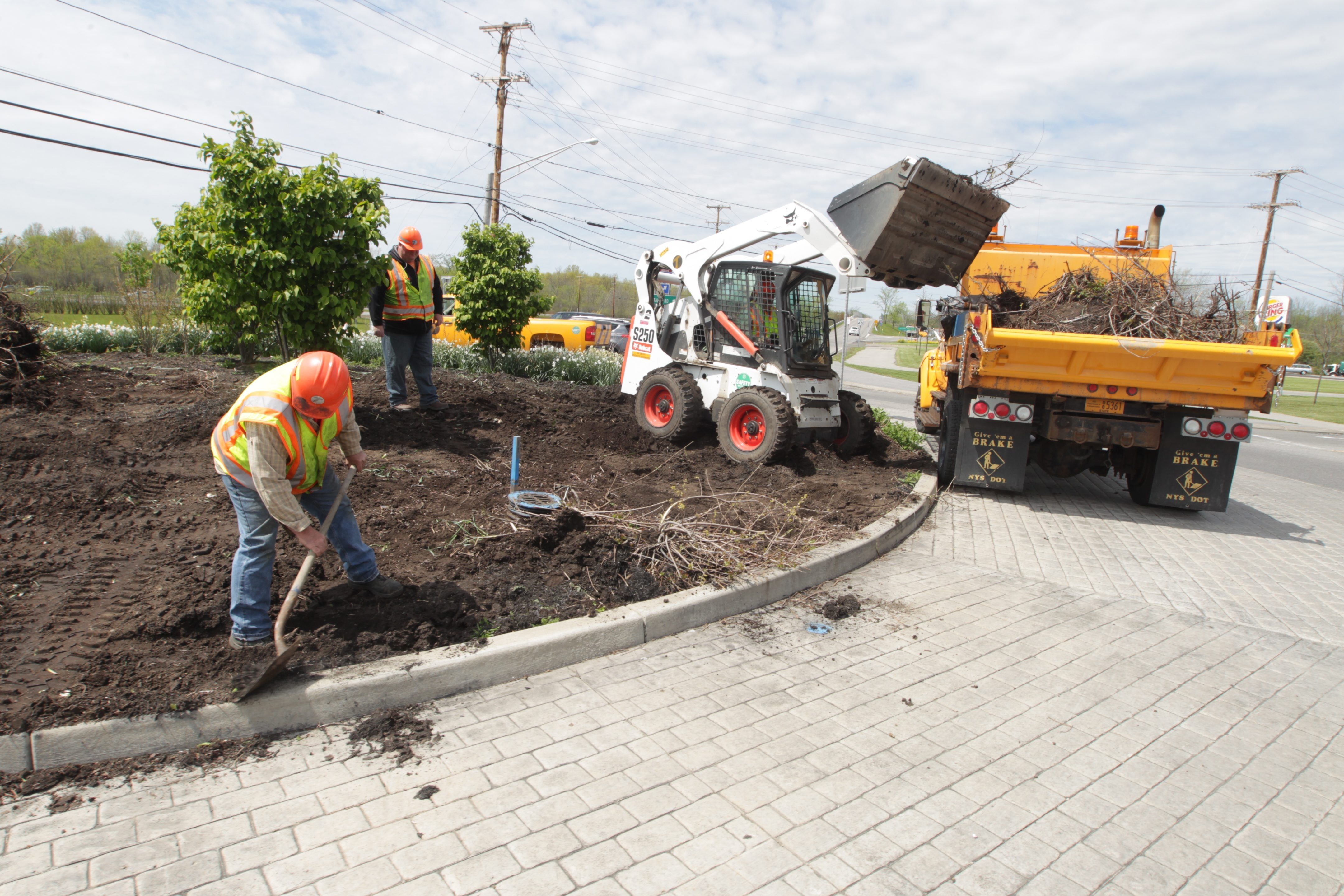 John Hickey/Buffalo News  State DOT workers, from left, John Wilson, Jim Hosie and John Georgal, in the tractor, work on makeover of the roundabout at the first exit off the south Grand Island Bridge.