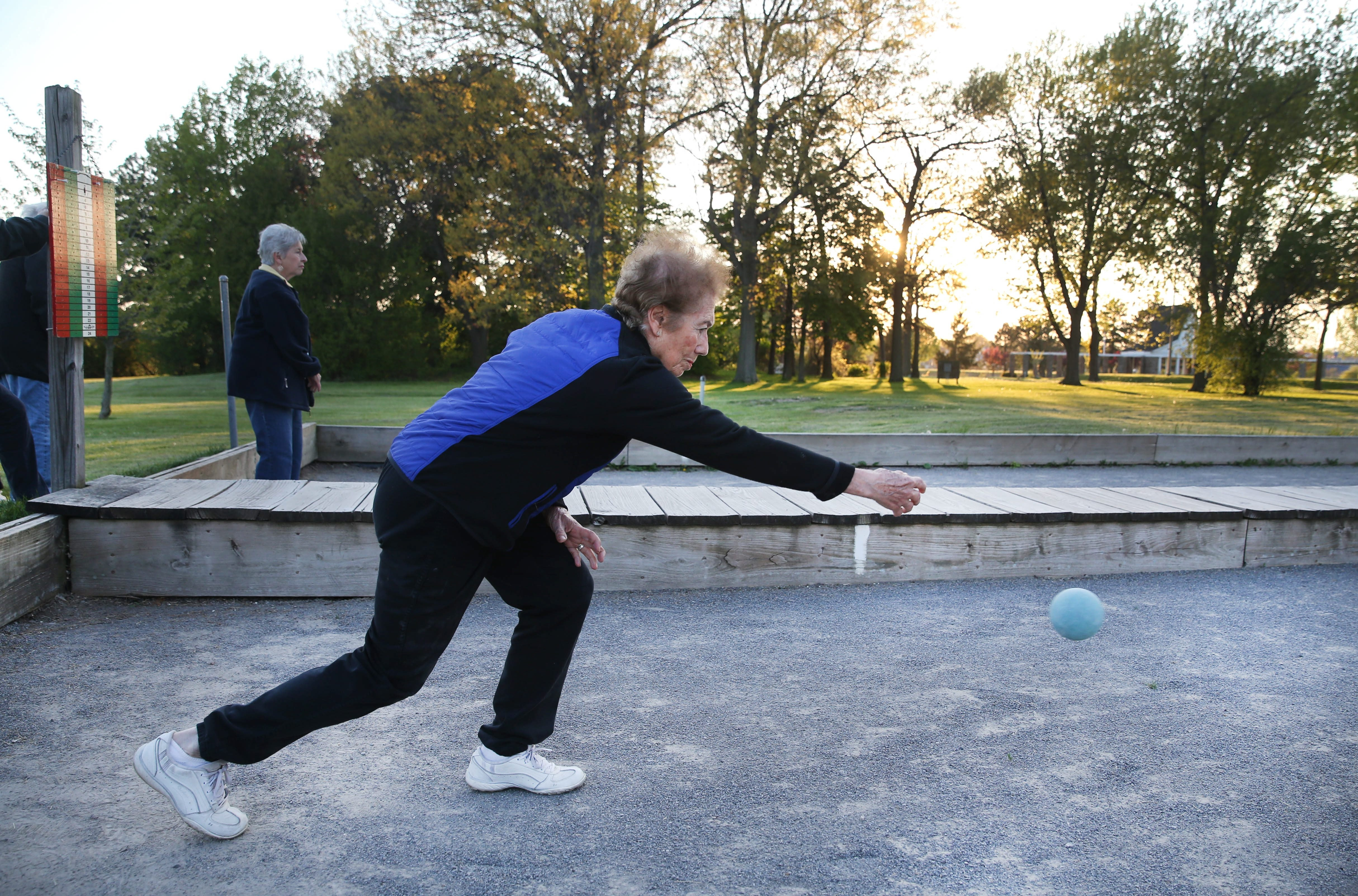Fun for all: On Thursday night, the women's teams play in the Hyde Park Bocce League in Niagara Falls. At top left, teammates Terry Smith, Kathy Culbreth and Marge George celebrate a good shot while Esther Runca, below, follows through on her shot. Bottom left, co-workers, from left, Tim Drews, Nick Manolakis, Mike Neth and Darren Zoldos enjoy a game at Illio DiPaolo's, and Anita Leo puts the ball in play at Hyde Park.