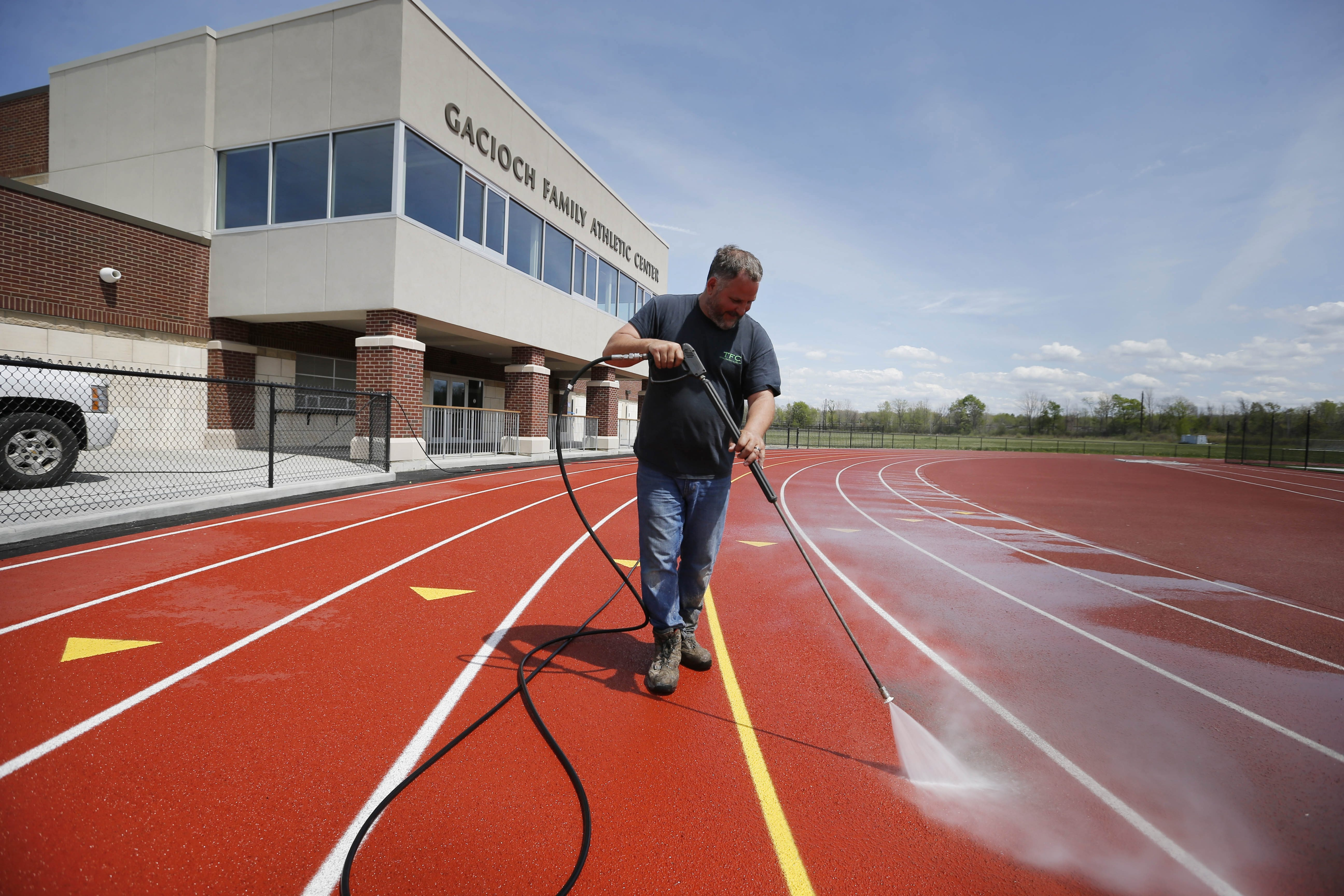 Gary Chase of Total Facility Care powerwashes the track at the new athletic complex at St. Francis High School on Thursday.