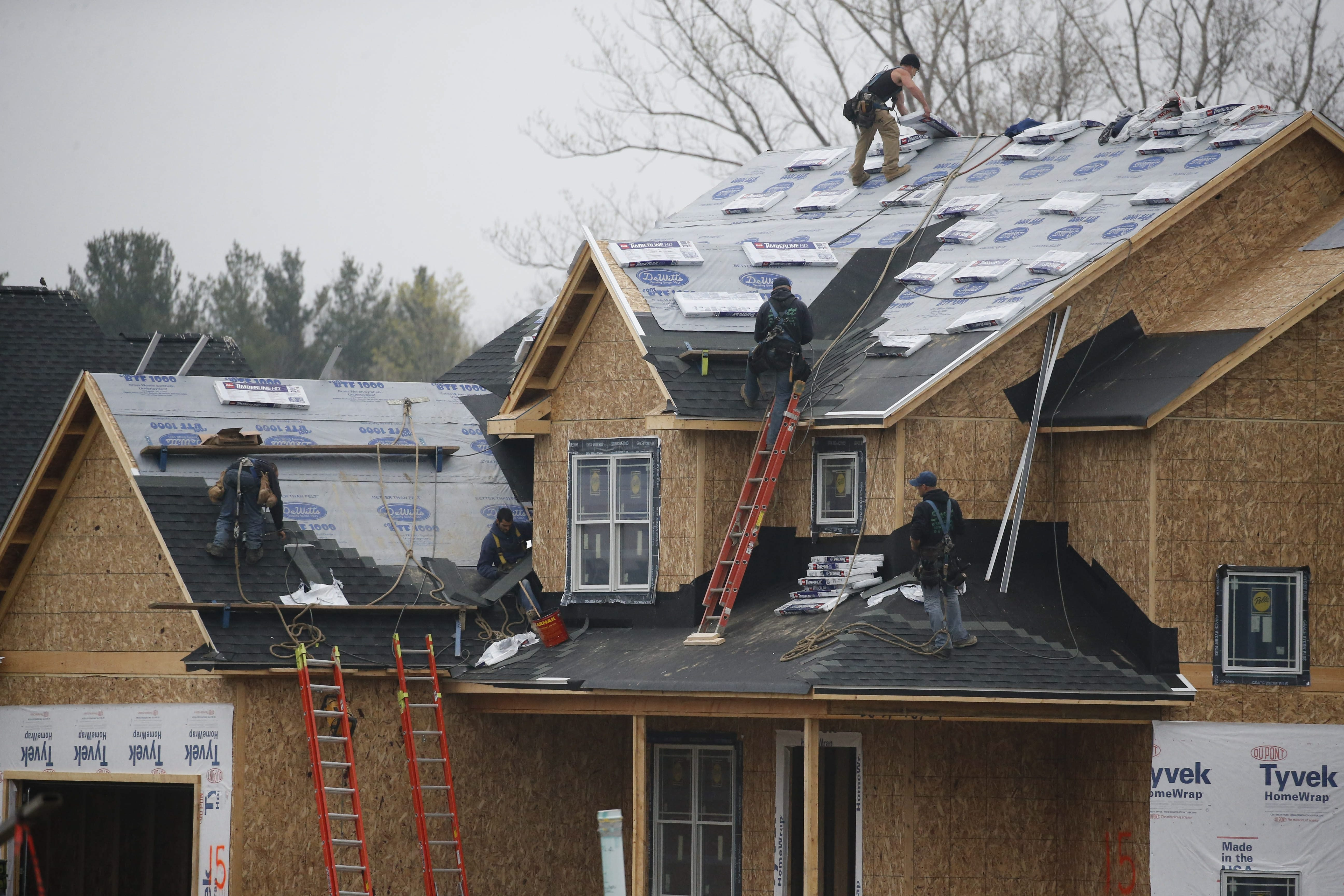 Derek Gee/Buffalo News  A crew of roofers works on a home in a new subdivision on Golden Oak Lane in Orchard Park last week.