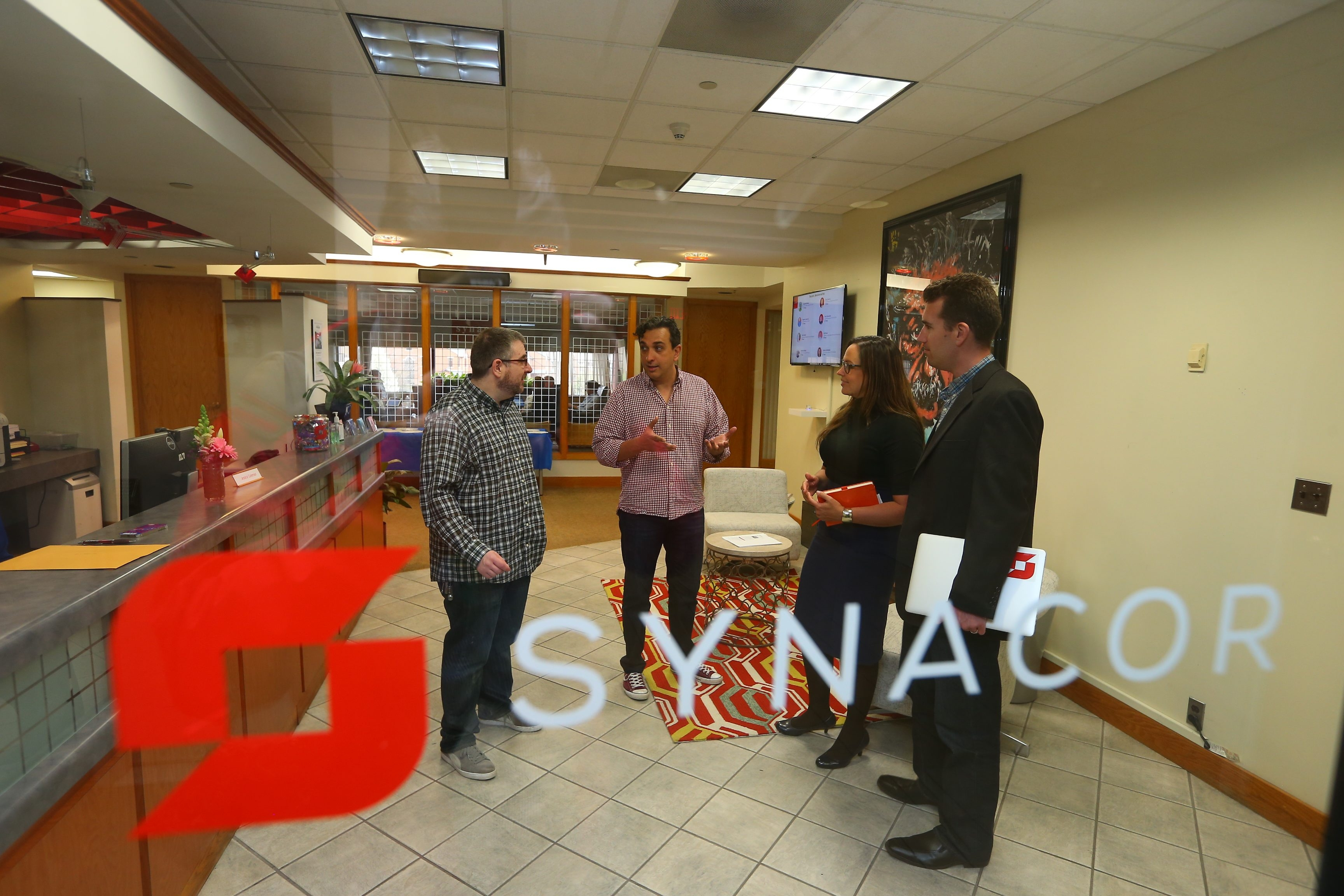 From left, John McDonald Sr., director of business operations; Mark Matias, senior systems architect; Erin Johnson, vice president of human resources; and John Kavanagh, senior director of products, meet in Synacor headquarters in Buffalo on Thursday.
