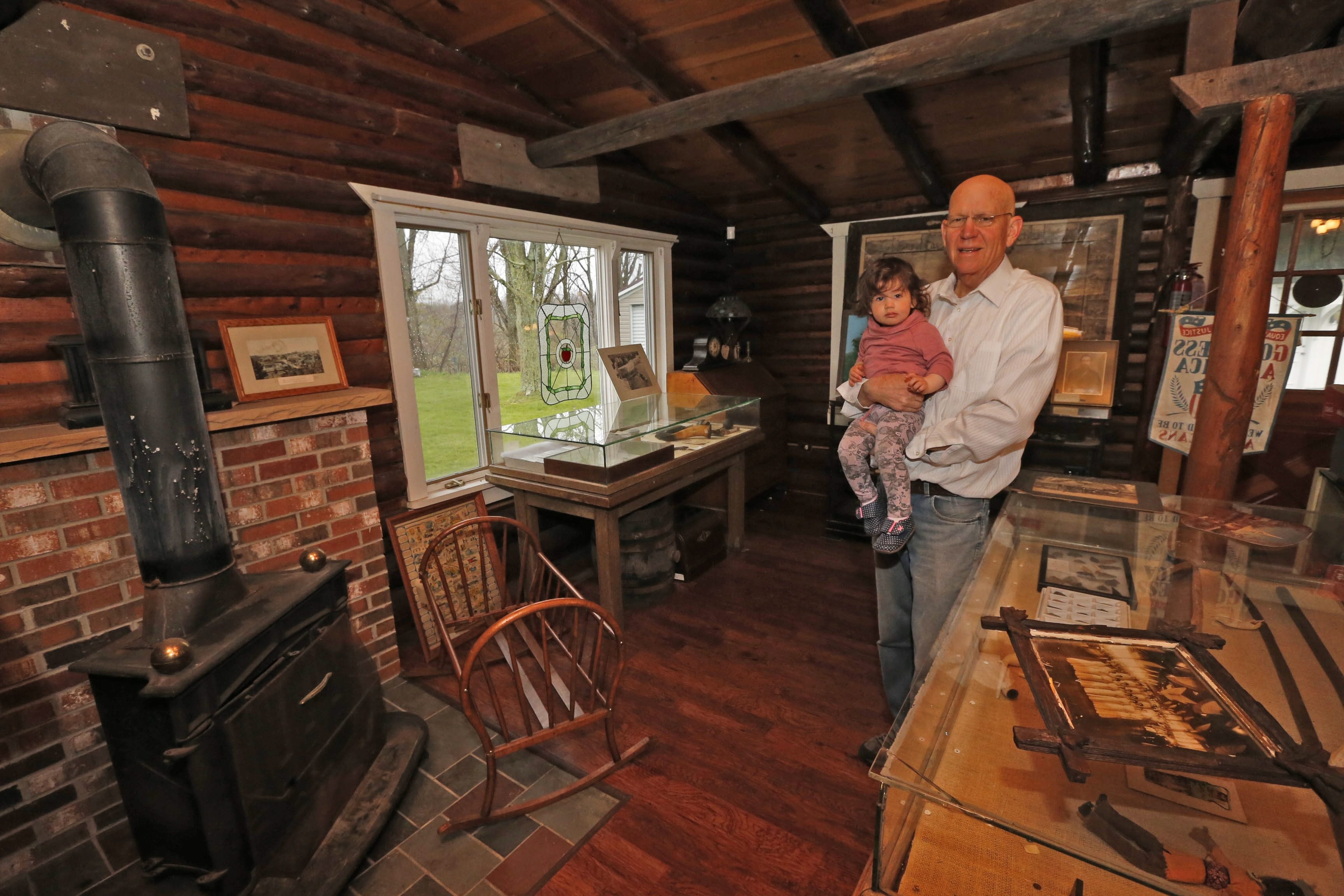 Bill Neidlinger, president of the Newfane Historical Society, holds his 18-month-old granddaughter, Makenna Keys, in the society's log cabin, which is reopening in time for the Apple Blossom Festival.