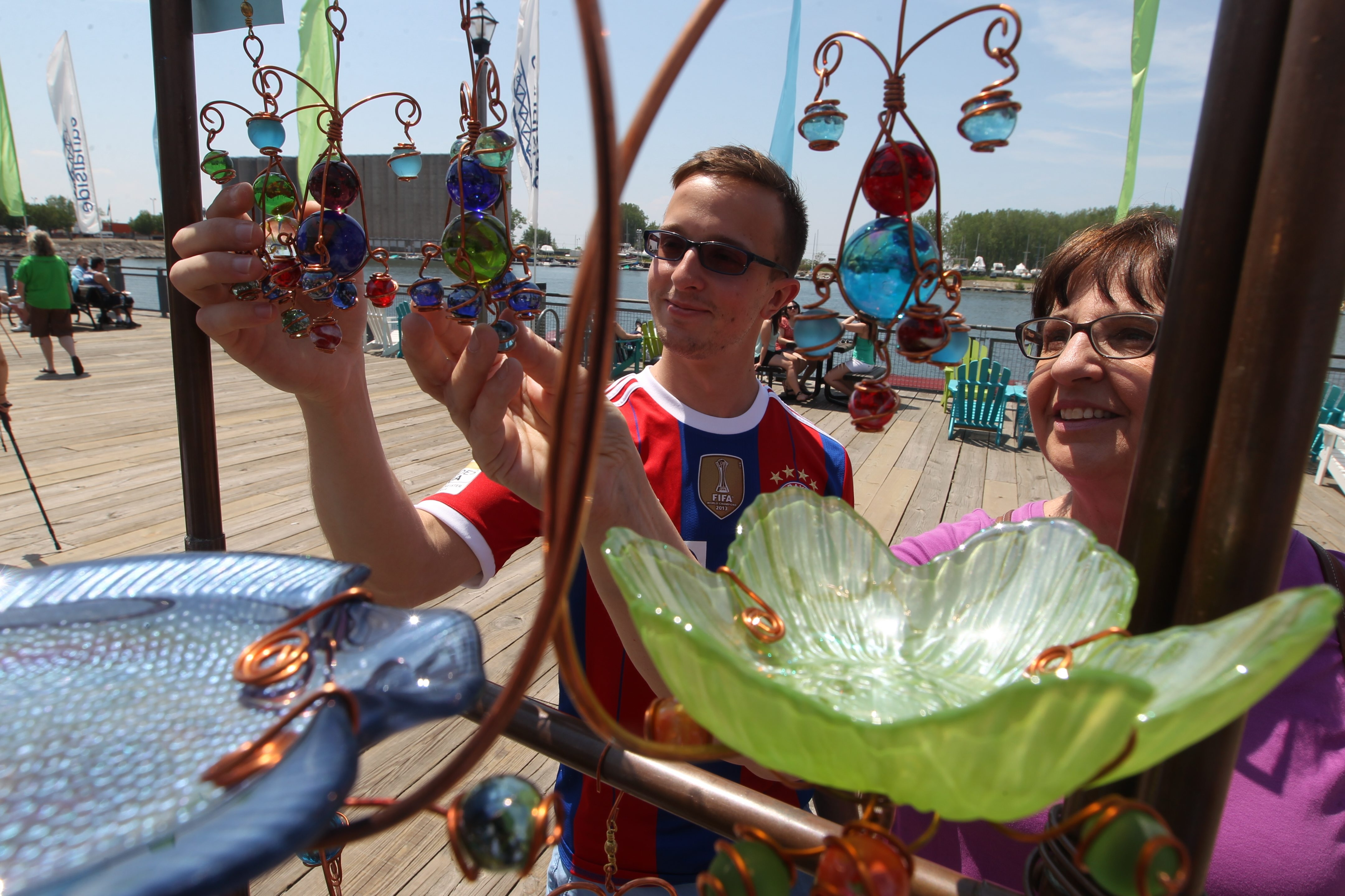 Adam Majewski and his mother, Linda Majewski, look at sun catchers Saturday at Creative Copper and Wire at the kickoff of the Artisan Market season on the boardwalk at Canalside.