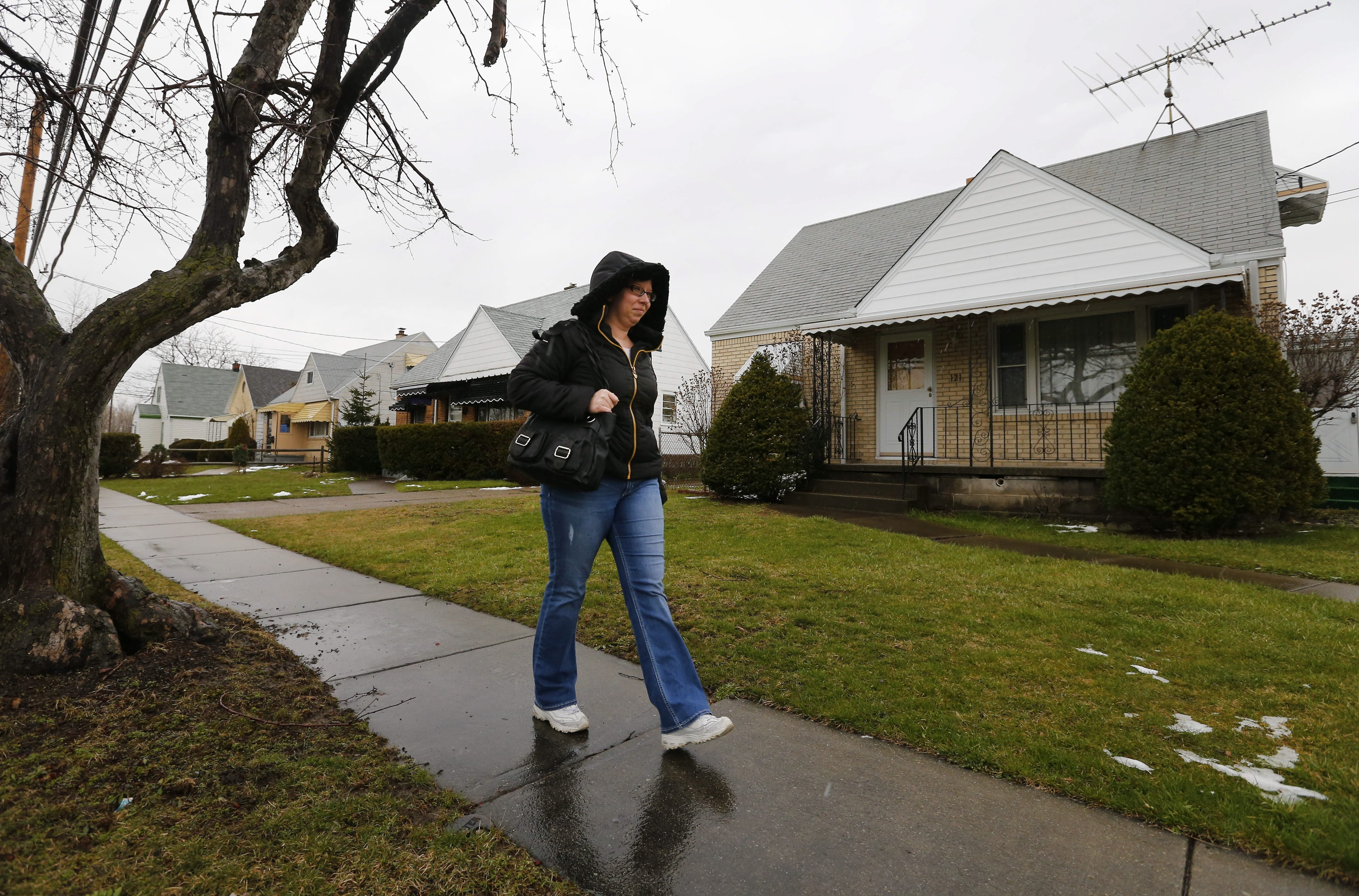First-time home buyer Jennifer Mueller walks past a house on Page Street she lost to other bidders.   (Mark Mulville/Buffalo News)