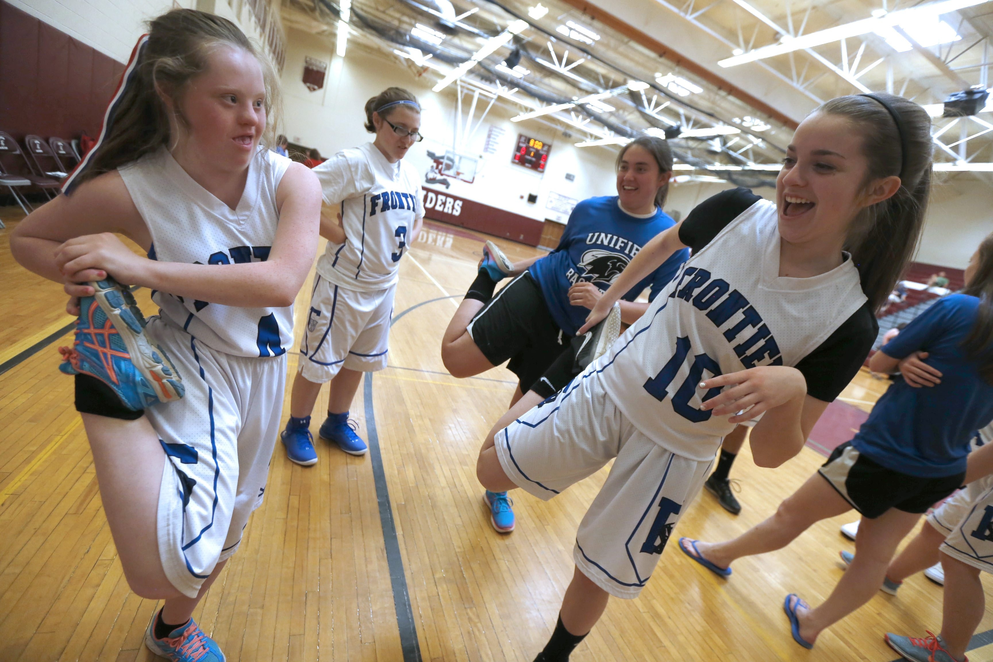 Frontier's Madison Fortuna, left, leads pregame stretching with teammate Kayle Filighera before the Falcons' recent game with Eden in Section VI Unified Sports, a collaboration between New York State Public High School Athletic Association and Special Olympics.