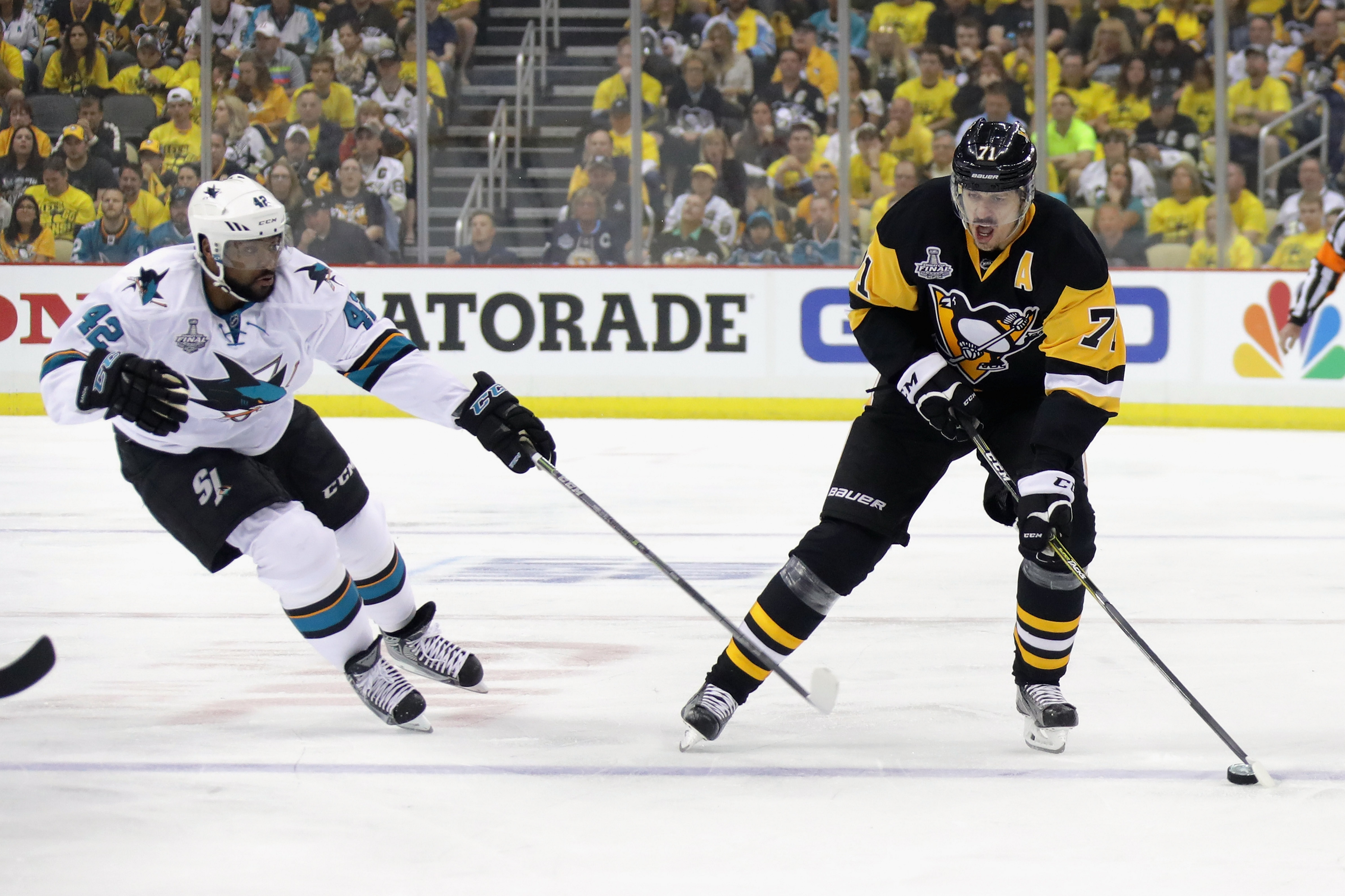Evgeni Malkin of the Penguins carries the puck into the San Jose zone against the Sharks' Joel Ward in the first period of Monday night's game in Pittsburgh.