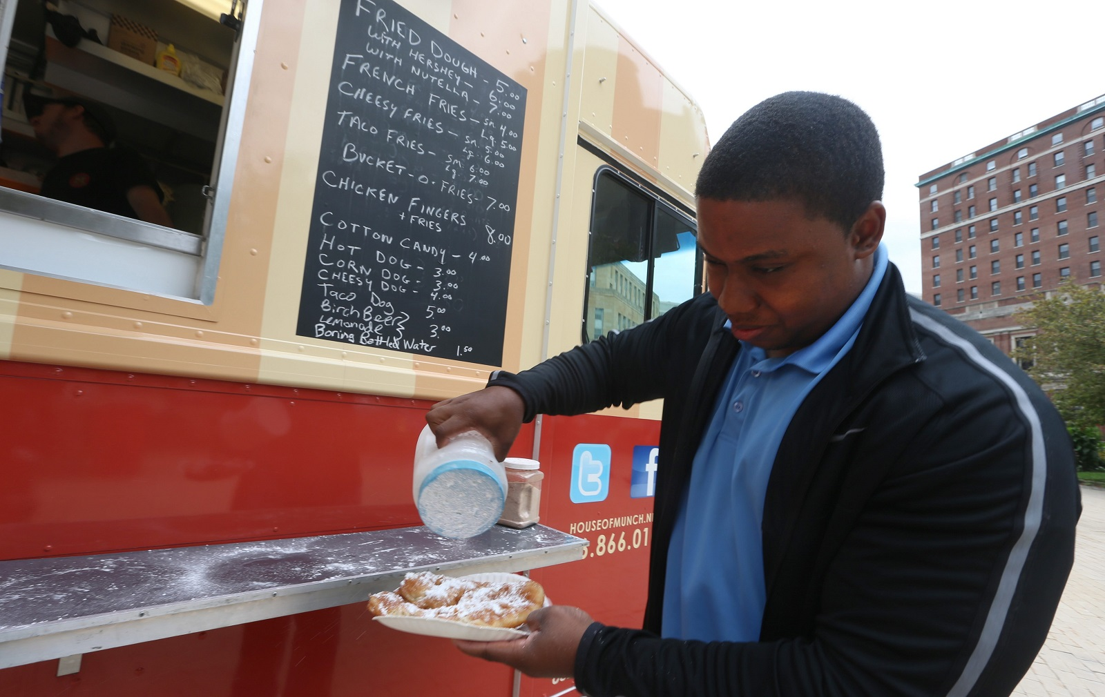 Isaiah Goins puts powdered sugar on fried dough at the House of Munch at Food Truck Thursday at Niagara Square in August 2015. (John Hickey/Buffalo News)