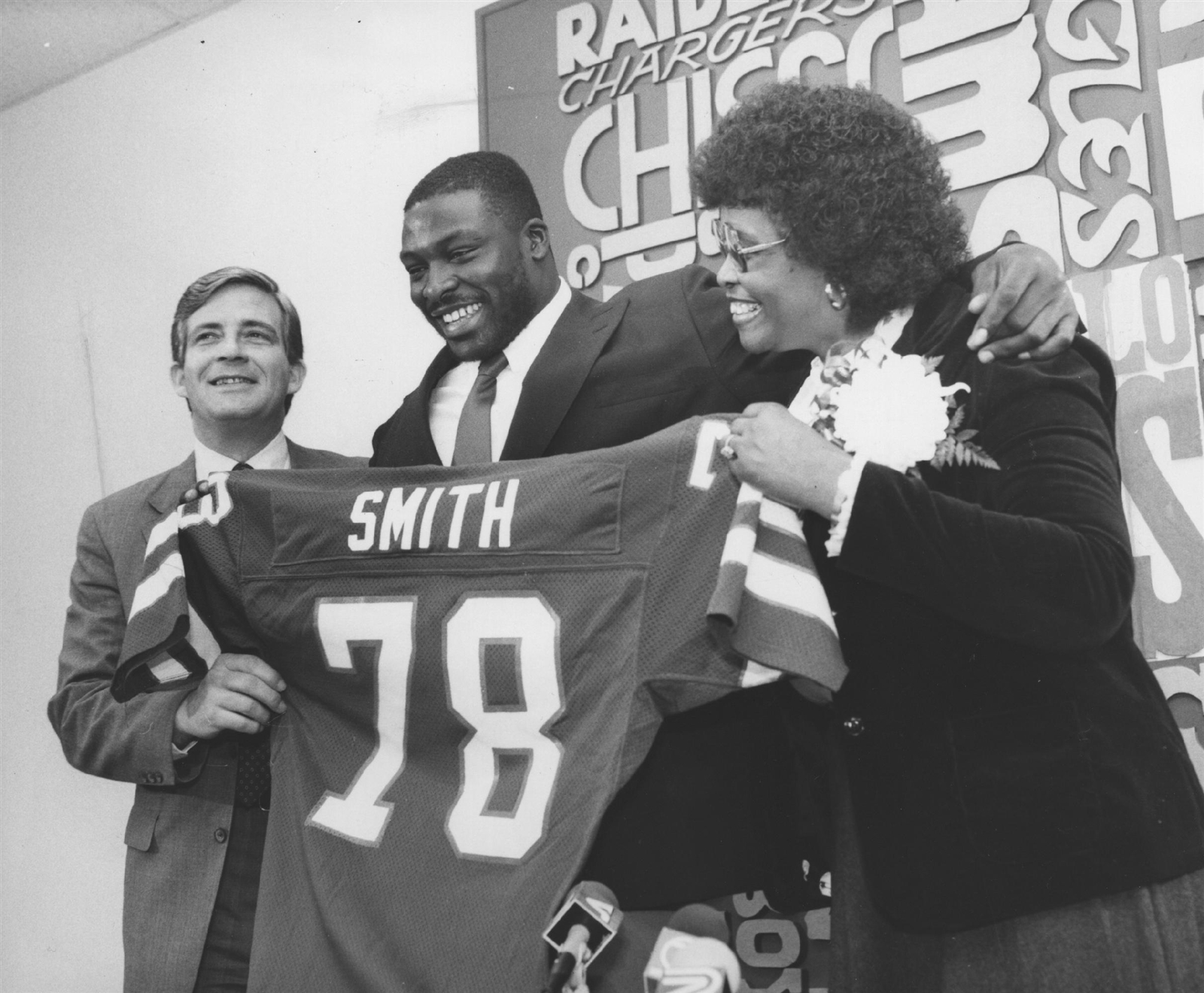 The Bills knew a certain defensive end out of Virginia Tech had great potential when they drafted him No. 1 overall in the 1985 NFL Draft. Here Bruce Smith shows off the jersey that would become legendary with coach Kay Stephenson and his mother, Annie Lee. (Buffalo News file photo)