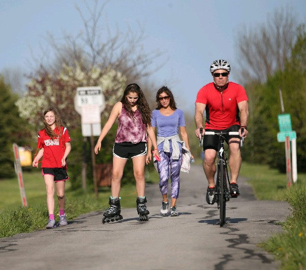 Dr. Marc Fineberg bikes on the Clarence bike path on a 75-degree day on Wednesday. He rides by Ella Petrulla, 11, left, her friend Eva Nuchereno, 11, and her friend's mother Norine Nuchereno. Wednesday's temperature was the highest recorded in Buffalo in 2016, but the mark will be eclipsed again today. (Sharon Cantillon/Buffalo News)