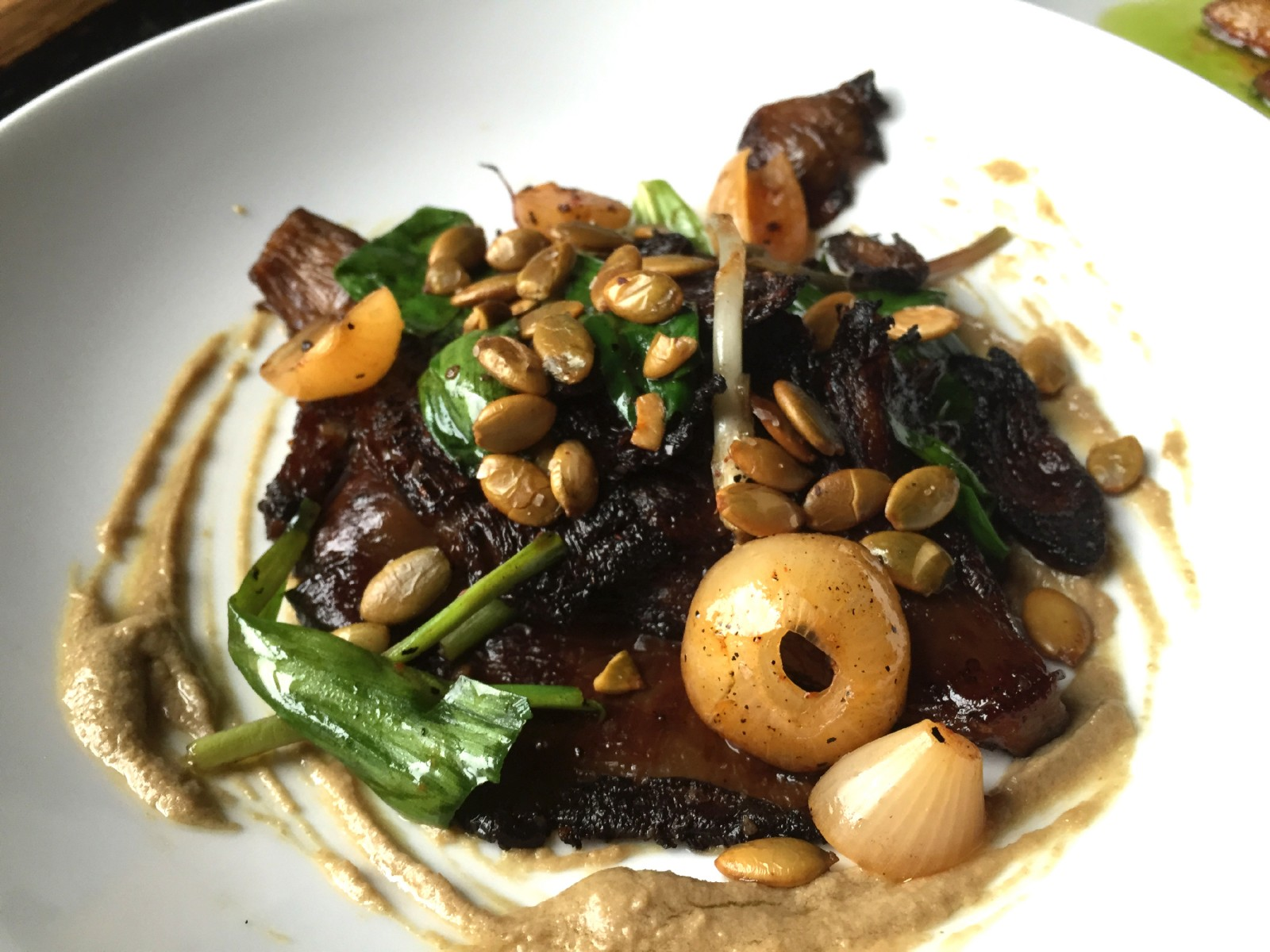 Flat 12 mushrooms, grown in Buffalo, are served with tangy shallots, toasted pumpkin seeds, fish-sauce-fermented ramps, and pumpkinseed sauce. (Christa Glennie Seychew/Special to The News)