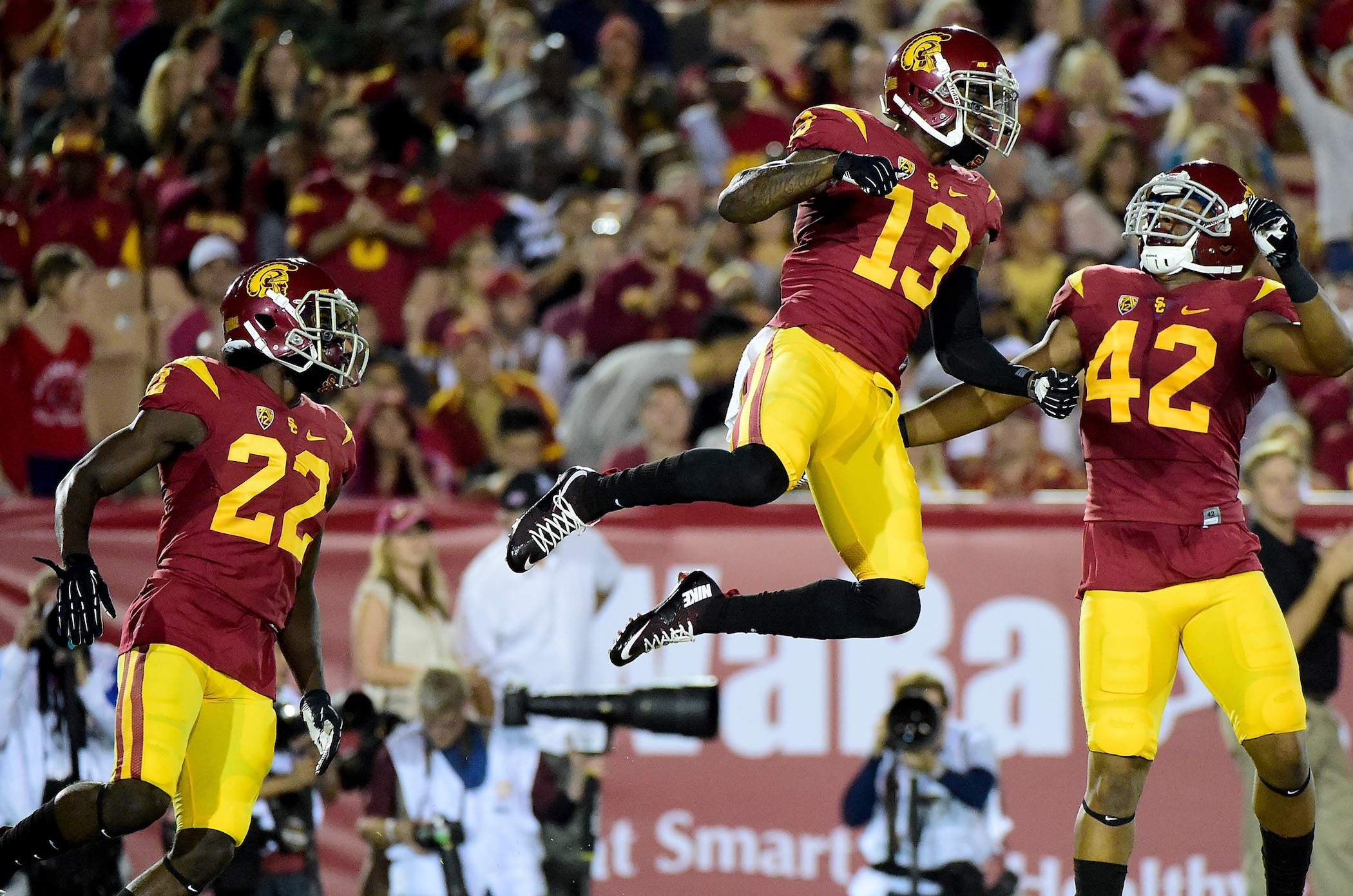 LOS ANGELES, CA - SEPTEMBER 05:  Kevon Seymour #13 of the USC Trojans celebrates his tackle after a punt with Uchenna Nwosu #42 and Leon McQuay III #22 against the Arkansas State Red Wolves at Los Angeles Coliseum on September 5, 2015 in Los Angeles, California.  (Photo by Harry How/Getty Images)