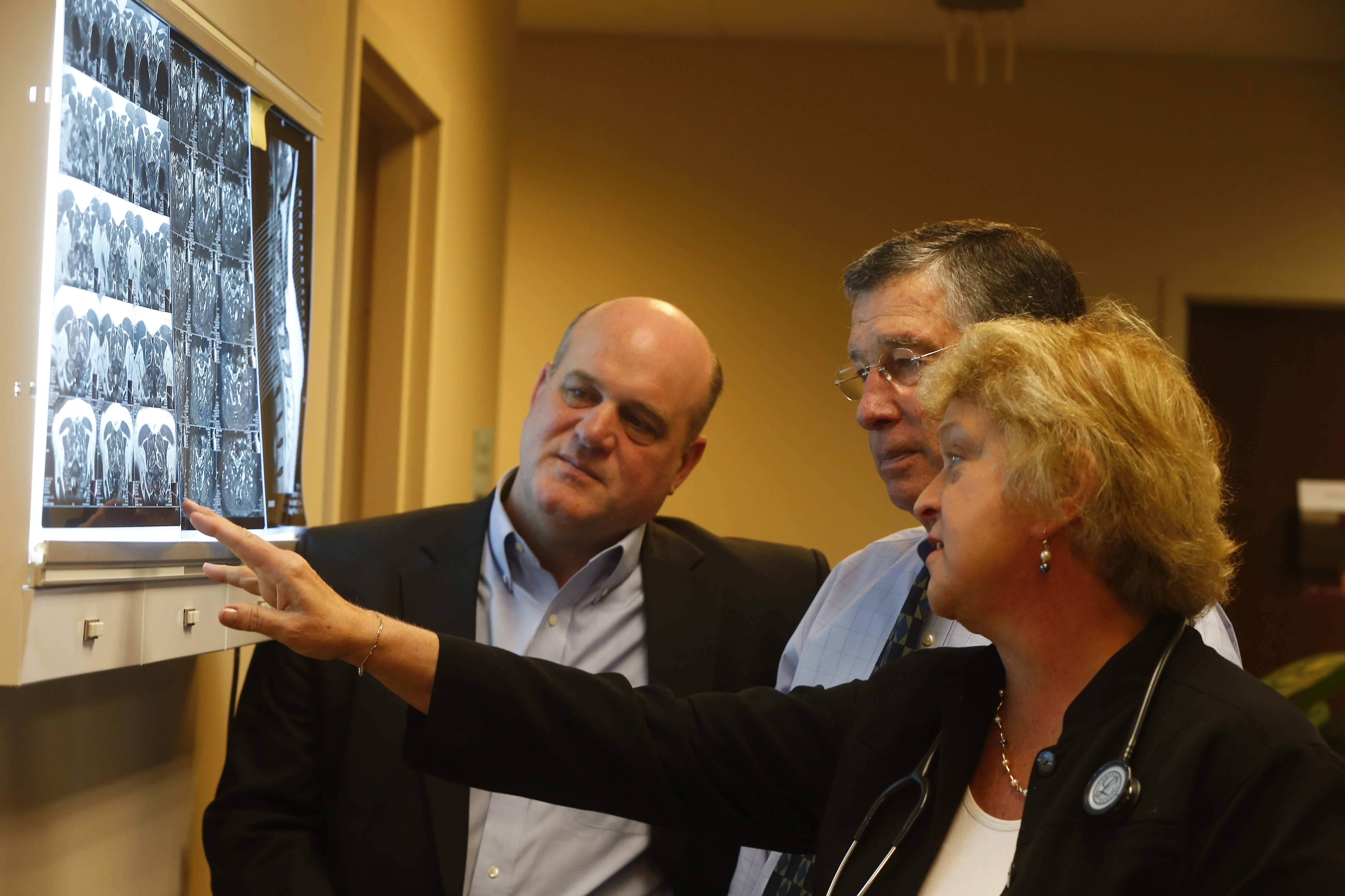 From left, doctors Christopher Kerr, Robert Milch and Nancy Nielsen look over an  x-ray at the offices of Gosy & Associates on Friday. The three doctors are filling in for Dr. Eugene Gosy, who is under federal indictment.