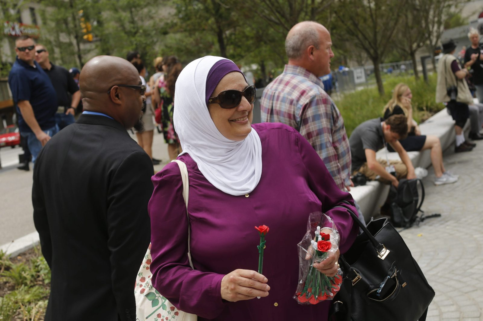 """Rose Hamid, who was born in Buffalo but has lived in North Carolina since 1987, hands out flower pens with the group """"Salam I Come in Peace"""" during protests outside the RNC in Cleveland, Ohio, Monday, July 18, 2016. (Photo by Derek Gee)"""